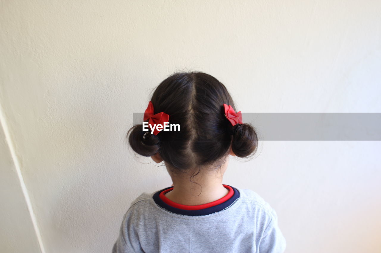 Rear View Of Girl With 9Against Wall