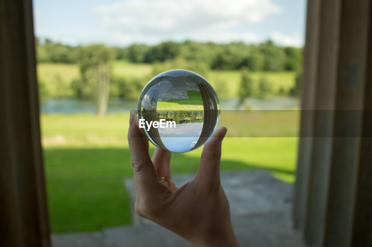 Cropped hand of woman holding crystal ball against sky