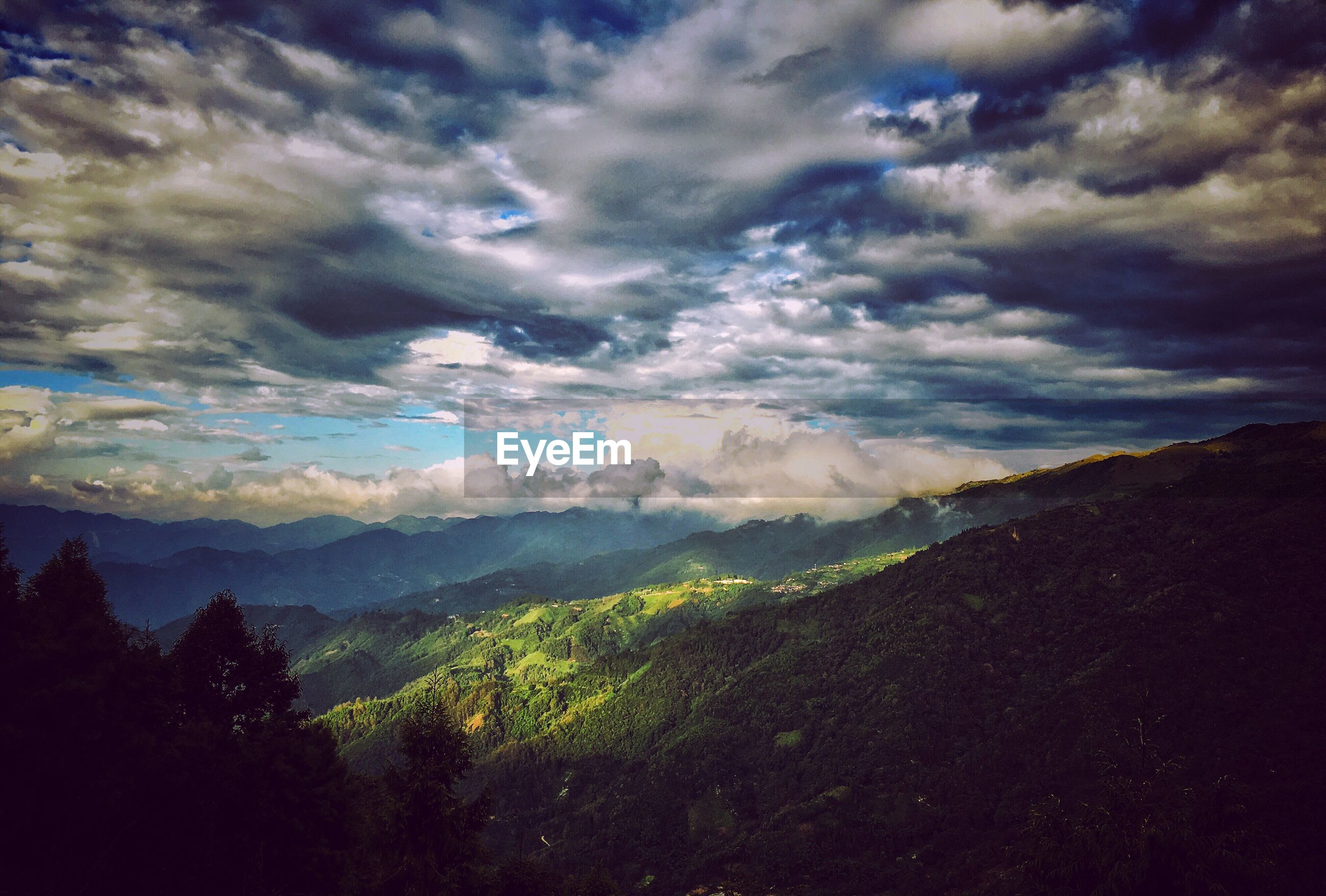 SCENIC VIEW OF MOUNTAIN LANDSCAPE AGAINST CLOUDY SKY