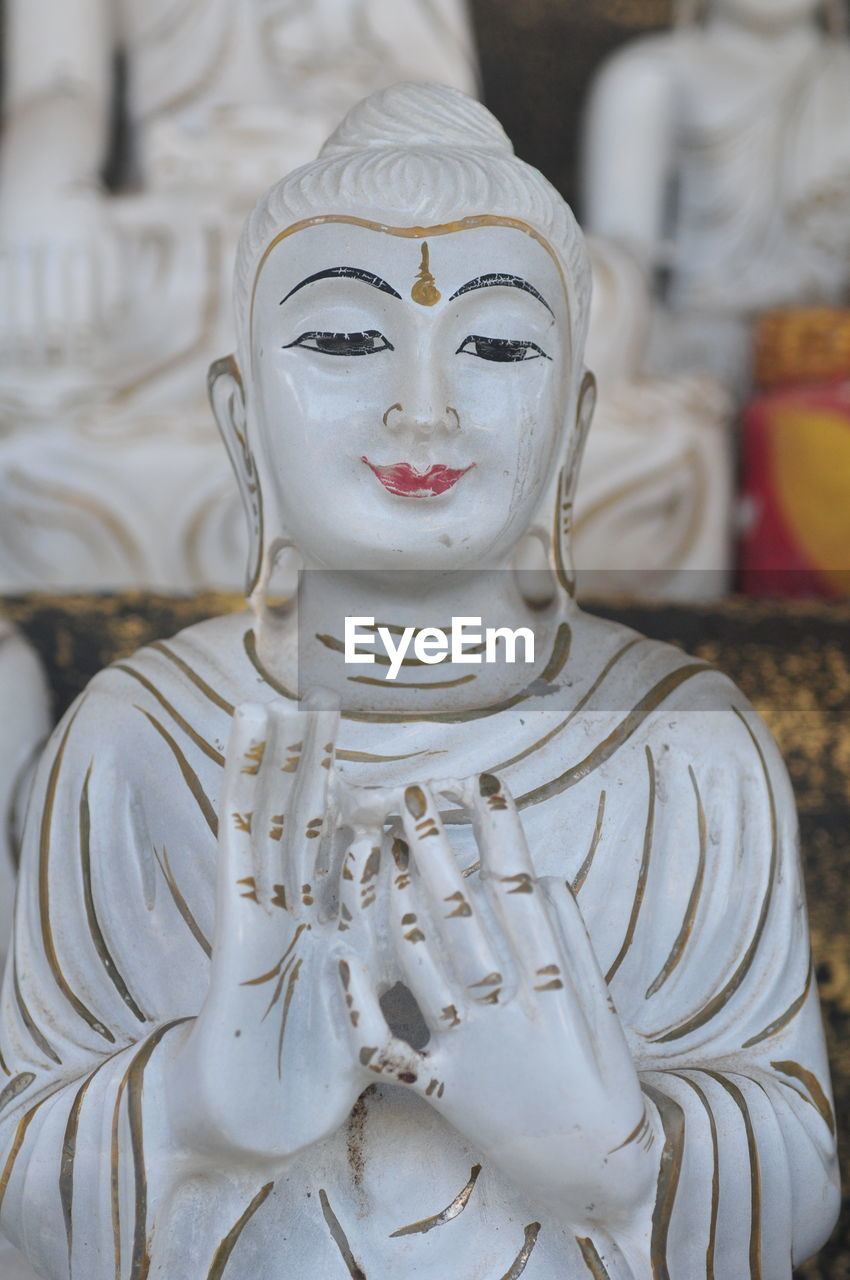 CLOSE-UP OF BUDDHA STATUE IN TEMPLE