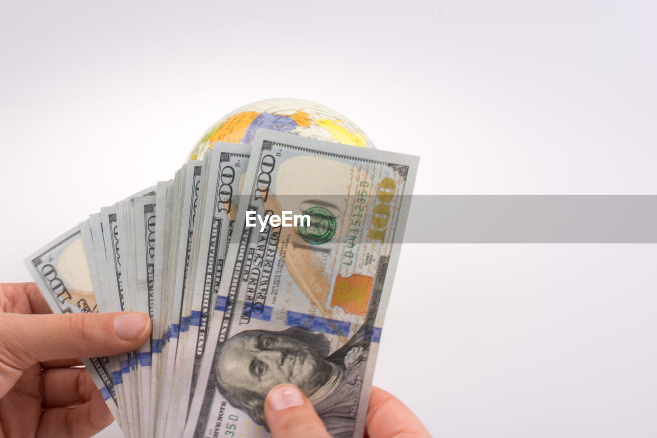 paper currency, currency, finance, holding, human hand, studio shot, human body part, business, white background, hand, wealth, one person, indoors, copy space, savings, close-up, cut out, finger, body part, economy