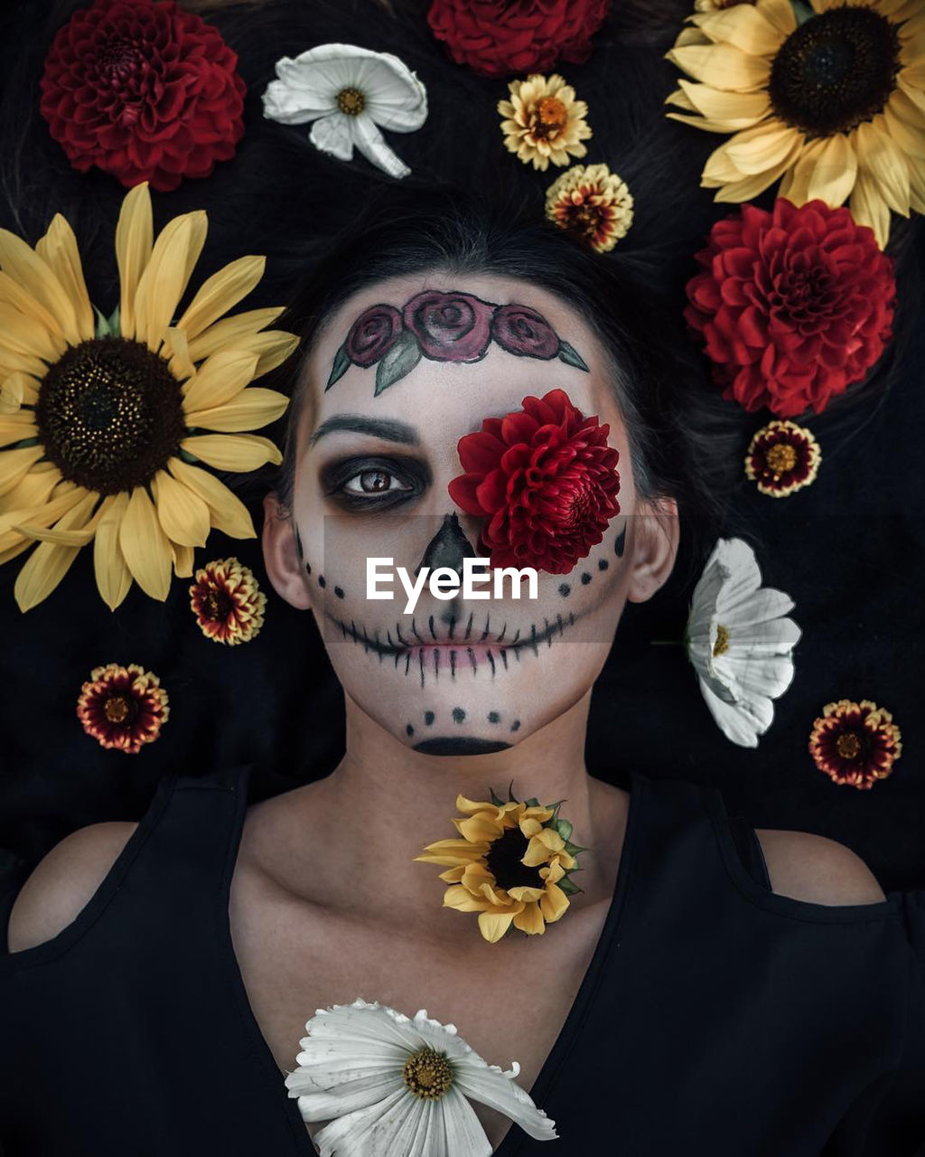 Directly above portrait of woman with halloween make-up lying amidst flowers