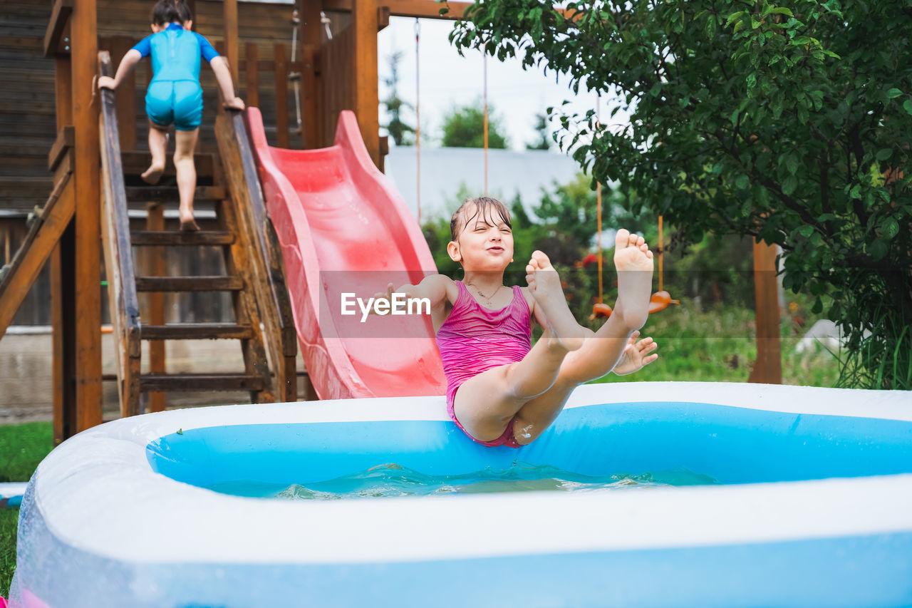 Full length of smiling girl playing on slide in swimming pool