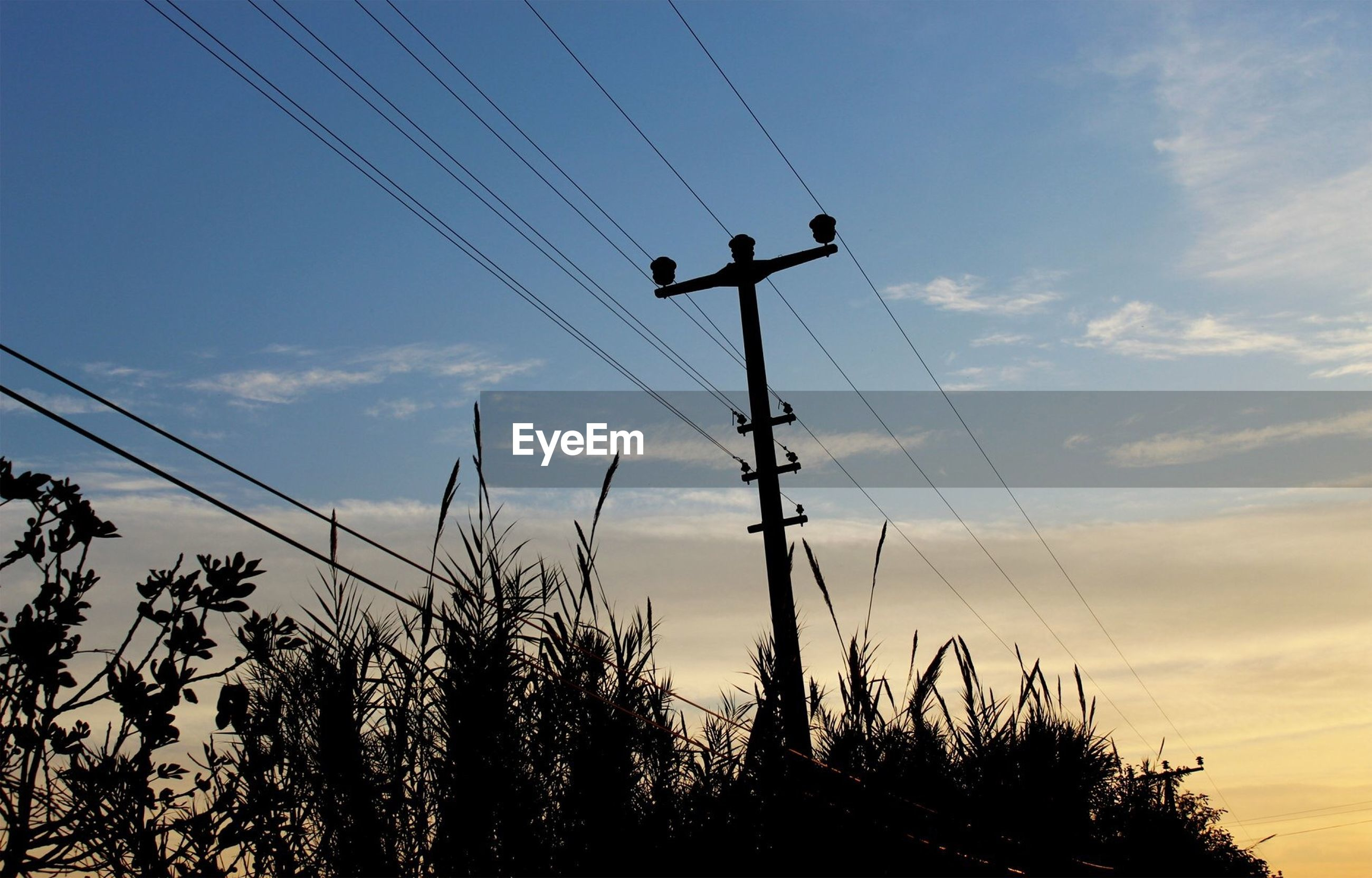 LOW ANGLE VIEW OF SILHOUETTE ELECTRICITY PYLONS AGAINST SKY DURING SUNSET