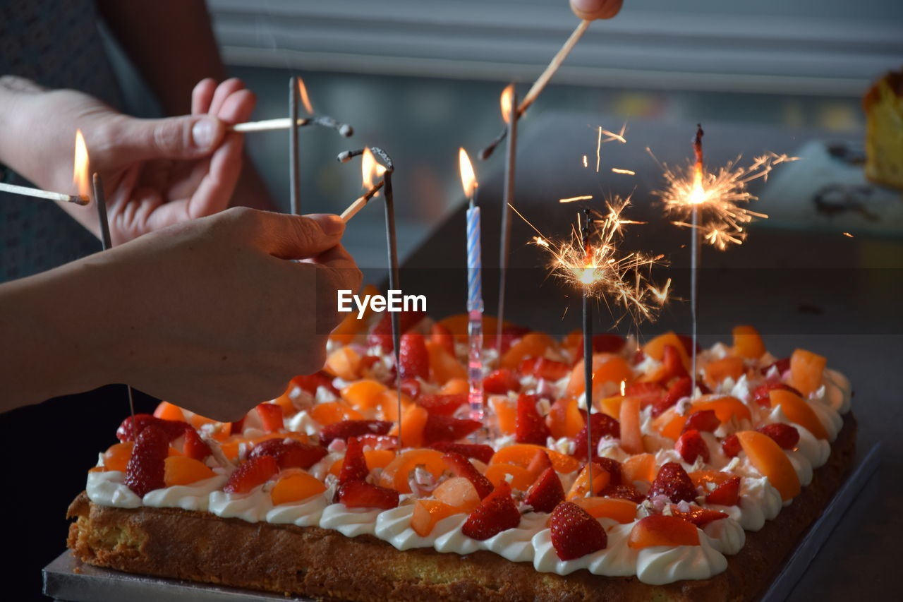 Close-up of hands lighting birthday candles
