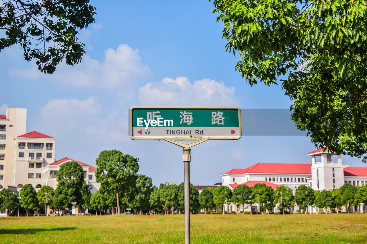 plant, tree, communication, text, sign, sky, western script, day, nature, green color, grass, guidance, information, built structure, no people, architecture, building exterior, outdoors, information sign, sunlight