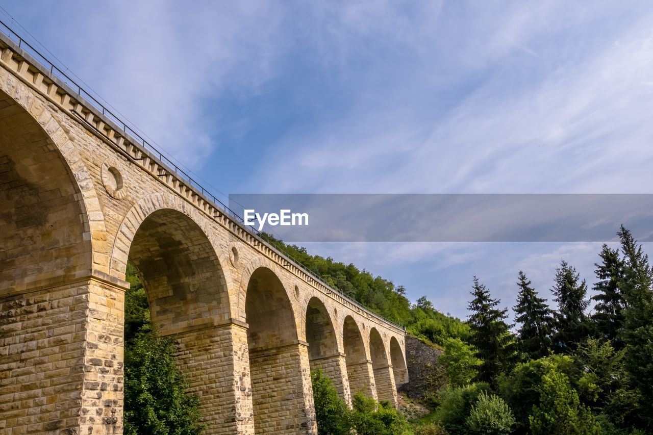 sky, architecture, cloud - sky, built structure, arch, nature, low angle view, tree, day, history, bridge, bridge - man made structure, no people, plant, connection, the past, outdoors, building exterior, ancient, travel destinations, arch bridge, arched
