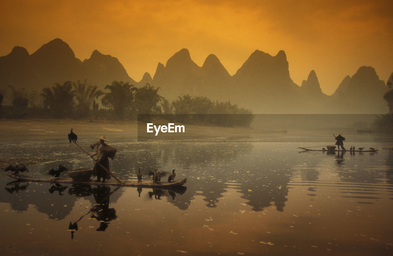 People With Birds On Boat In Lake Against Mountains During Sunset