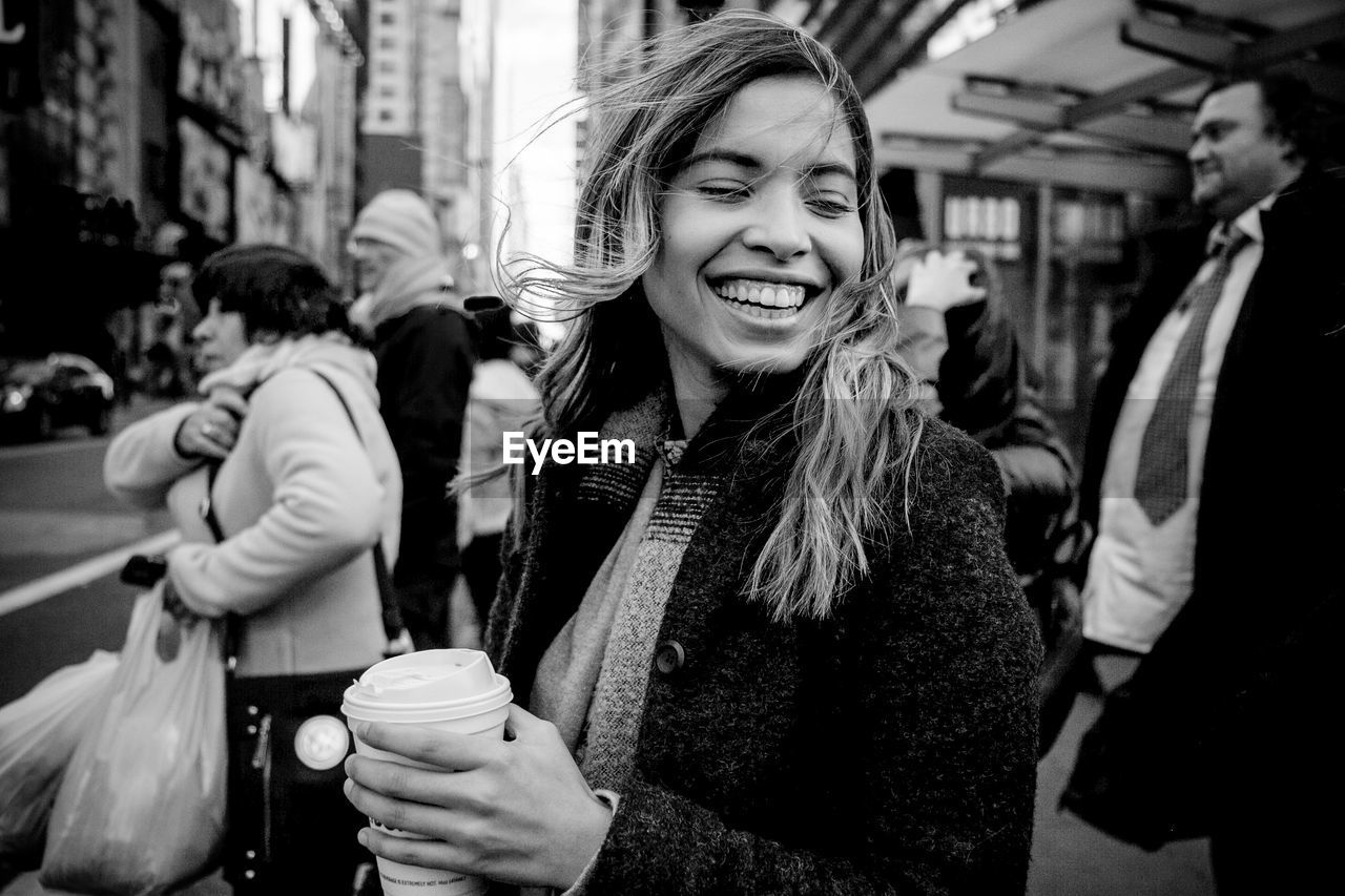 Happy Young Woman Holding Drink While Walking On City Street