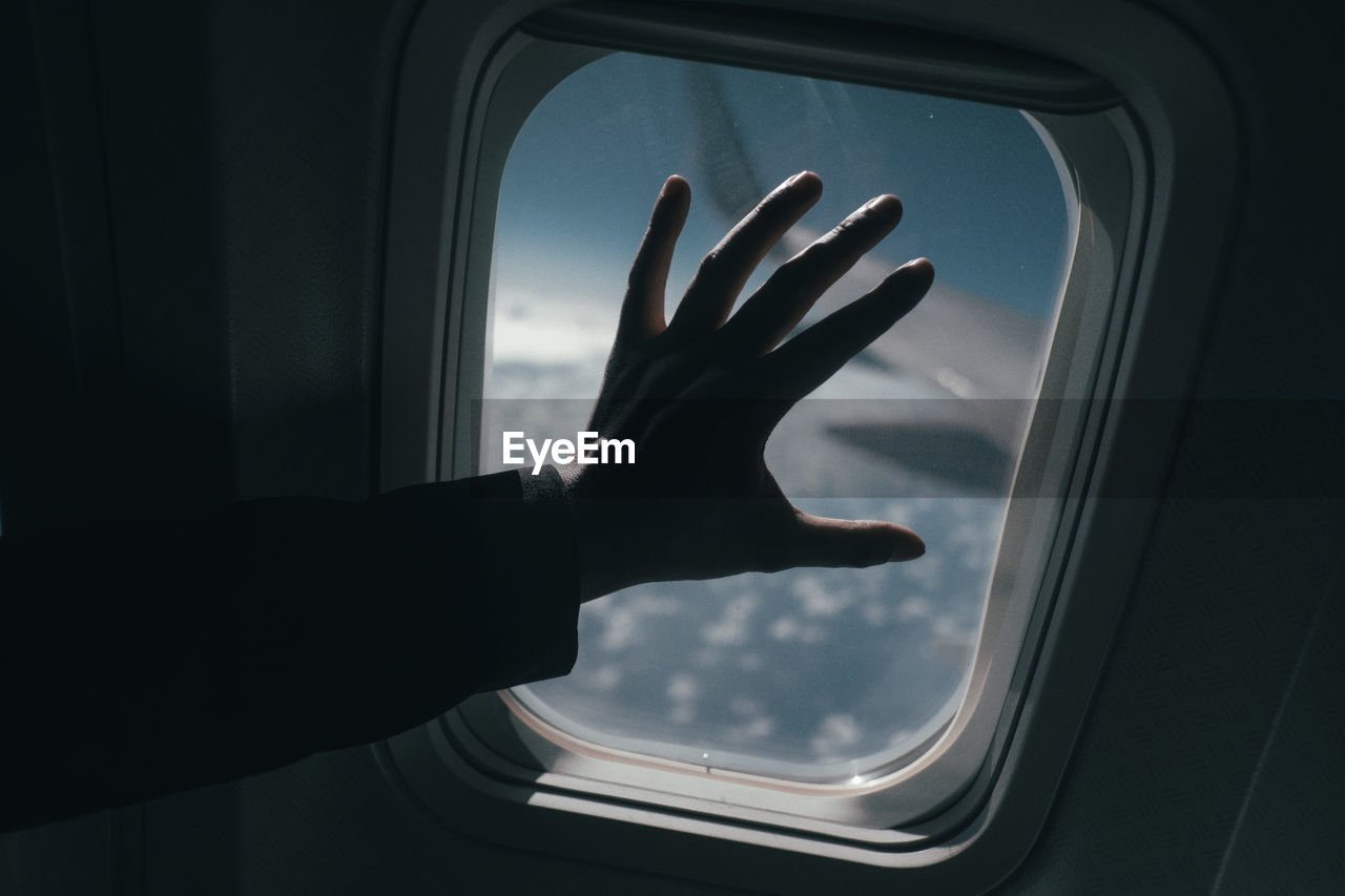 Cropped Silhouette Hand On Airplane Window