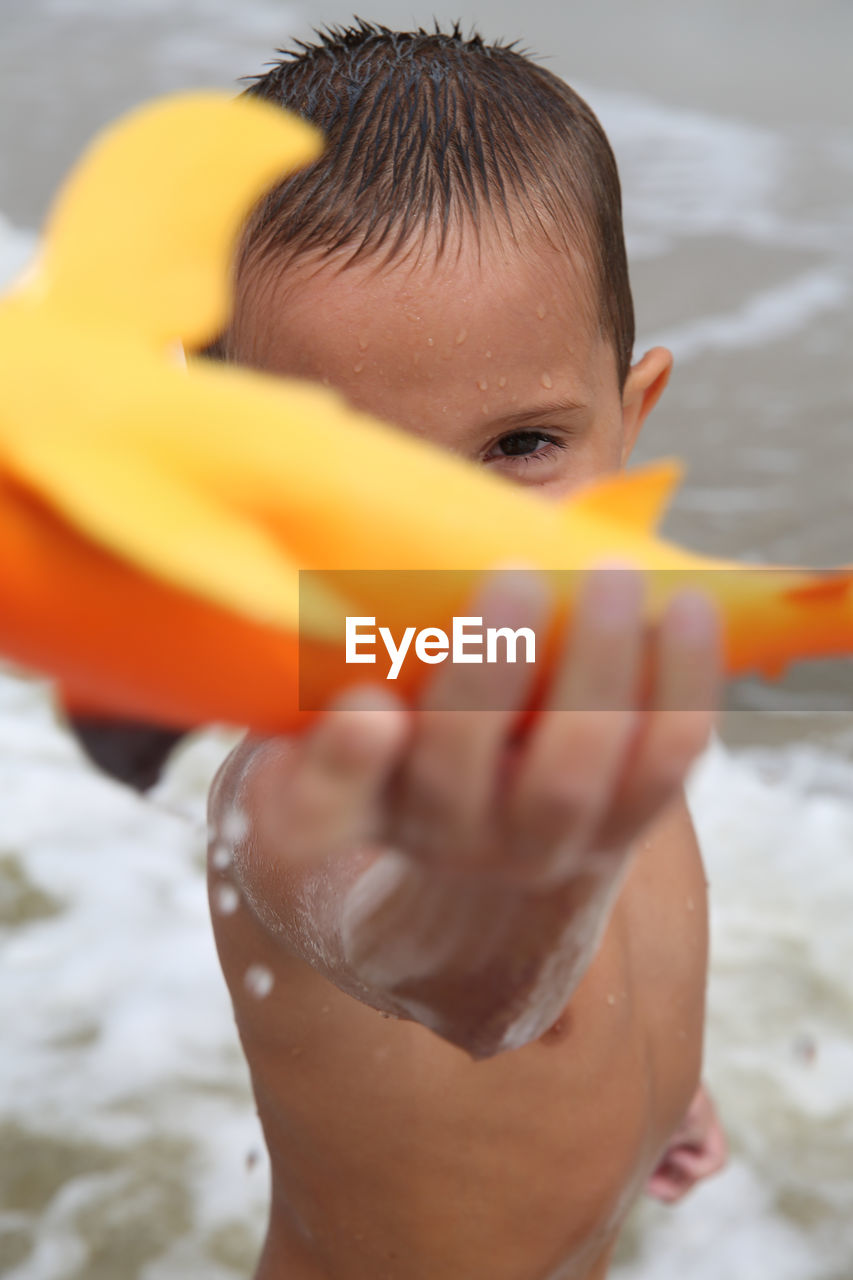 one person, childhood, real people, water, leisure activity, lifestyles, day, close-up, boys, headshot, outdoors, sea, human body part, human hand, people