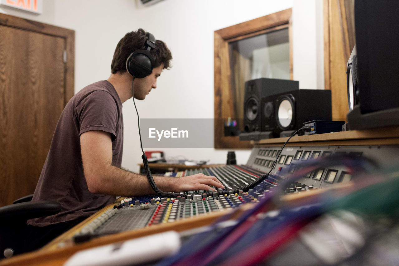 music, technology, young adult, computer, one person, sitting, concentration, musical instrument, arts culture and entertainment, sound recording equipment, real people, audio equipment, side view, indoors, recording studio, waist up, young men, sound mixer, selective focus, adult, profile view, keyboard