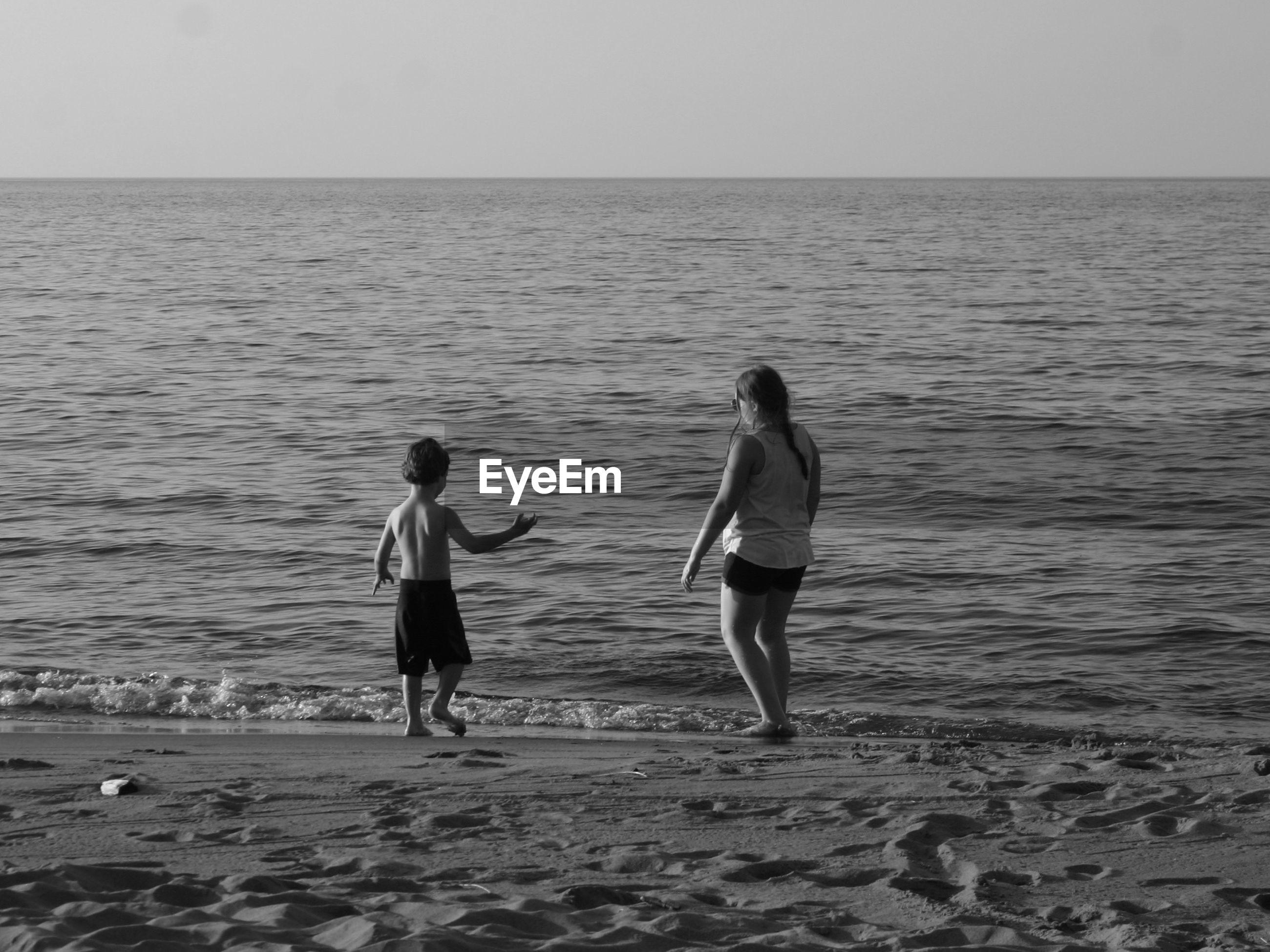 Rear view of siblings enjoying at beach against sky