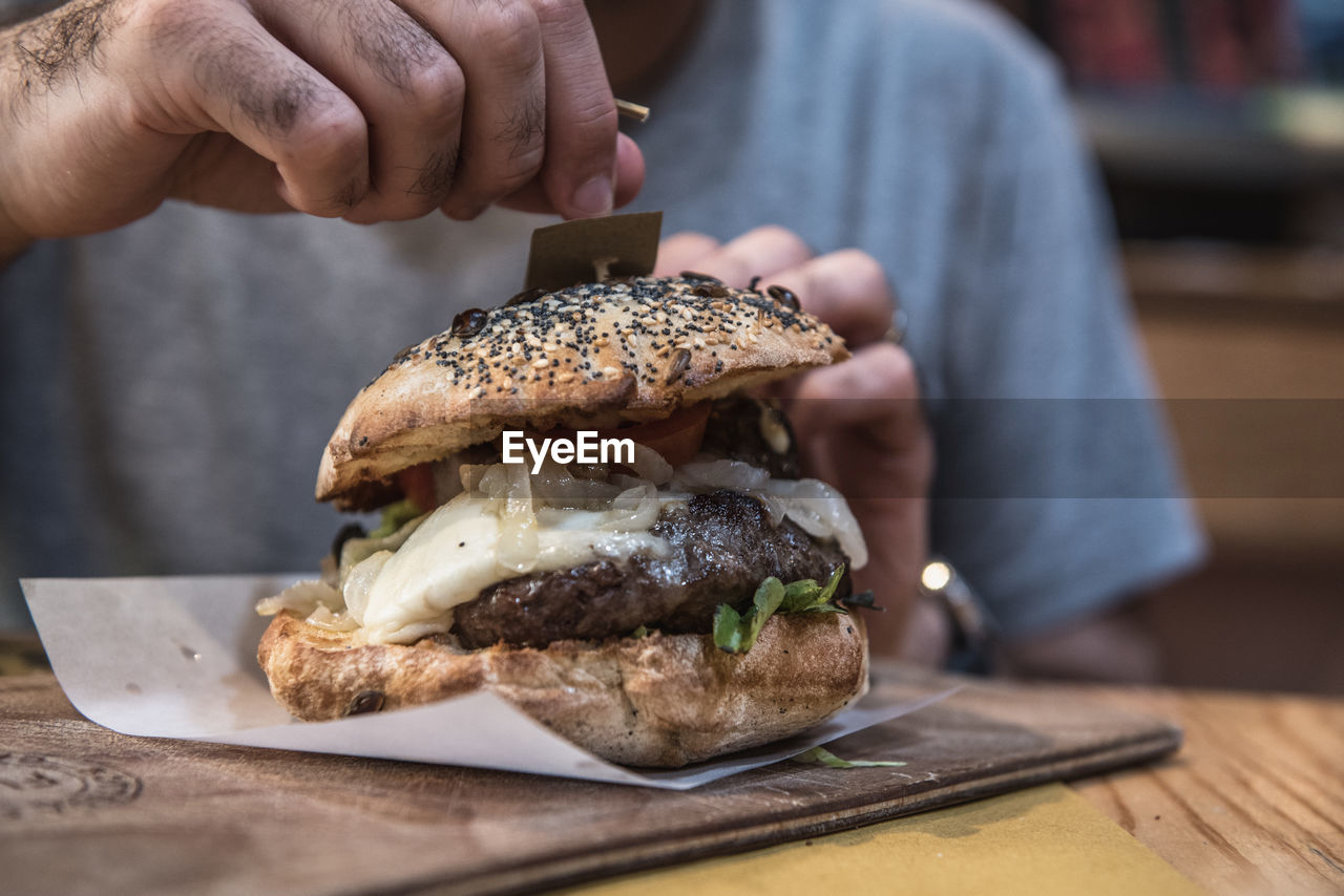 Close-up of hand holding burger on table