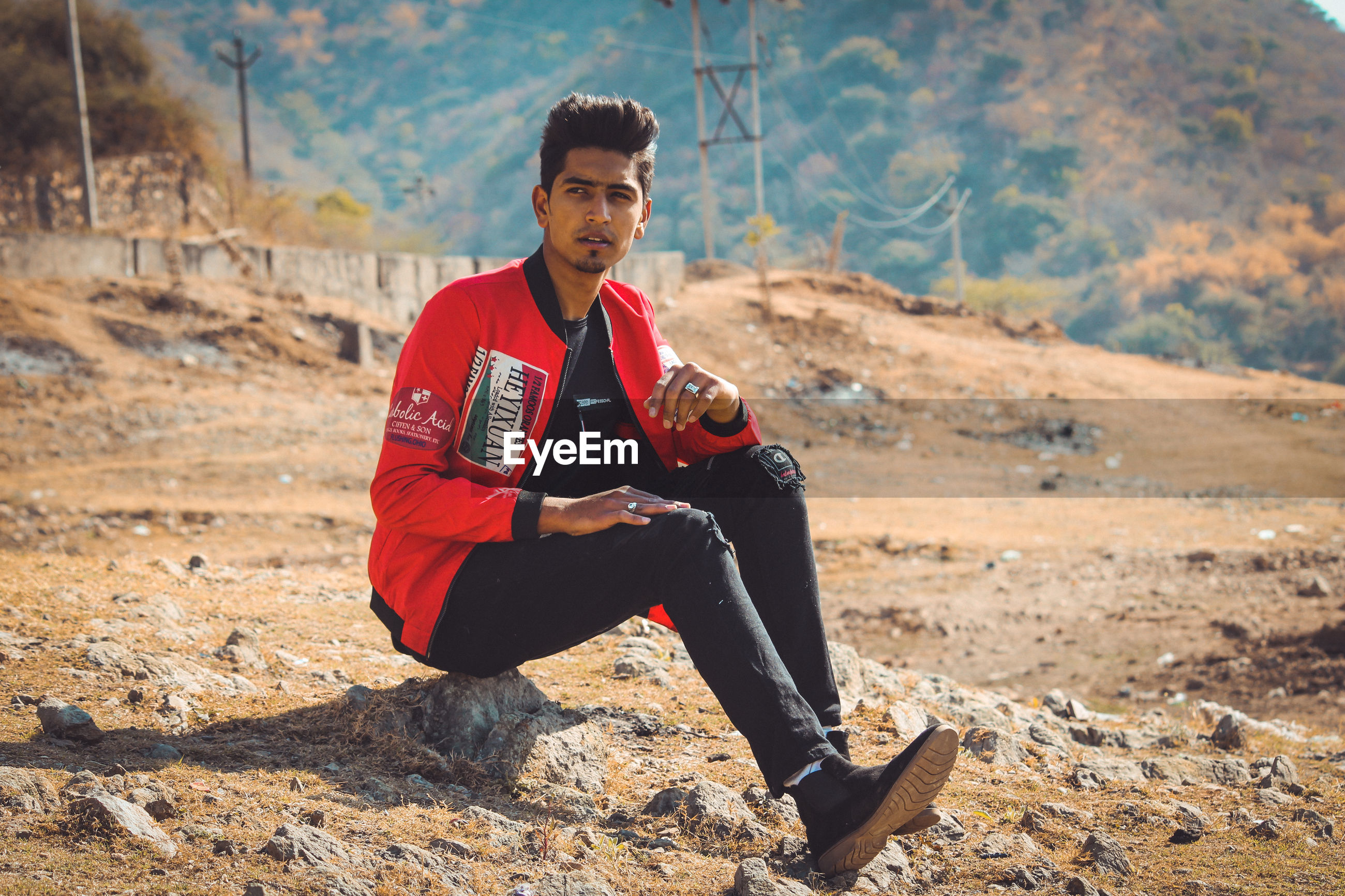 Handsome young man looking away while sitting on rock