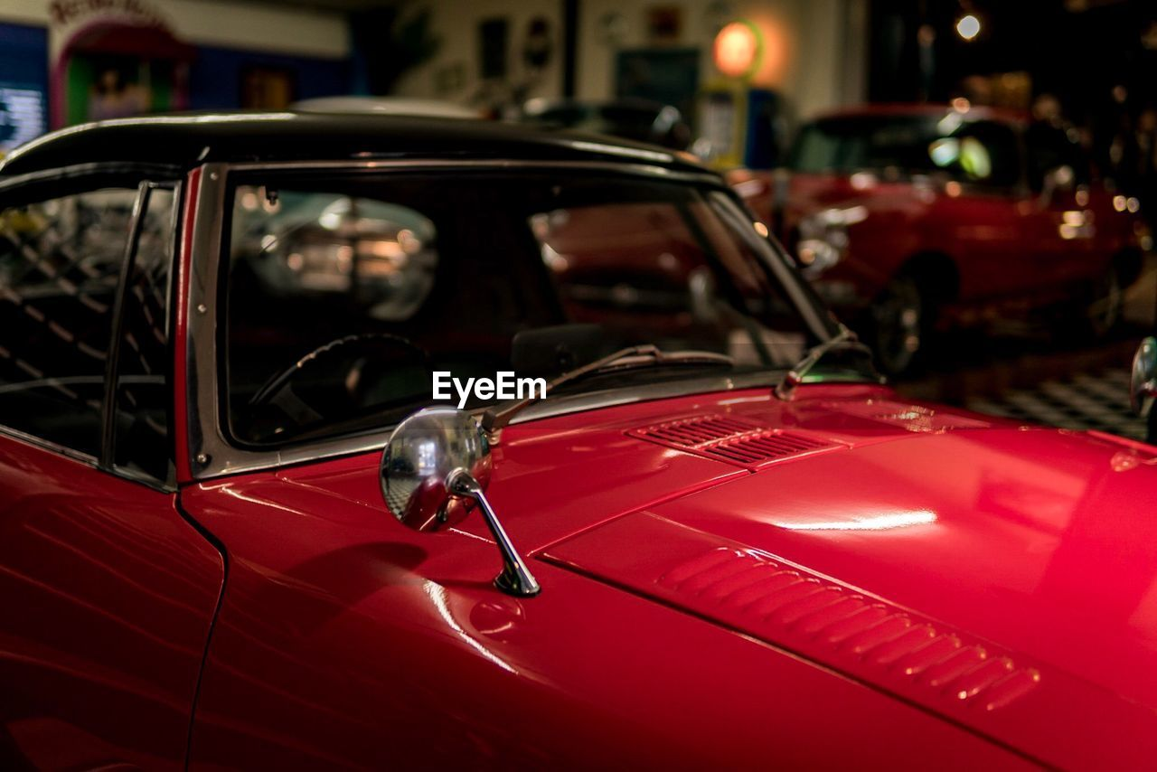 car, red, land vehicle, transportation, mode of transport, focus on foreground, no people, close-up, outdoors, night