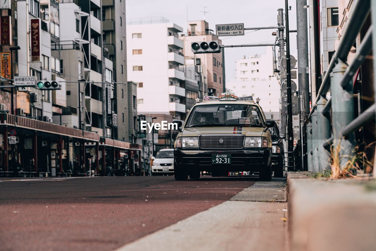 city, mode of transportation, building exterior, transportation, architecture, built structure, land vehicle, motor vehicle, street, car, building, selective focus, day, incidental people, road, outdoors, city life, city street, residential district, travel, apartment