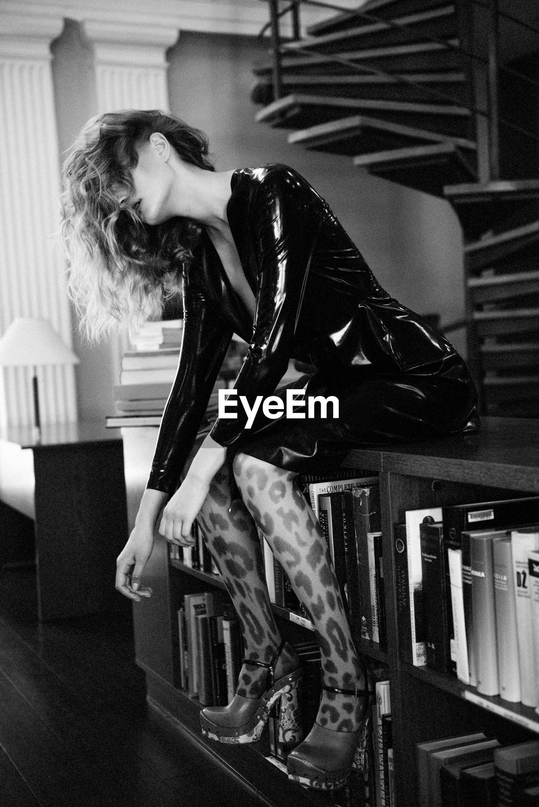 Side view of young woman in latex clothes sitting on bookshelf at home