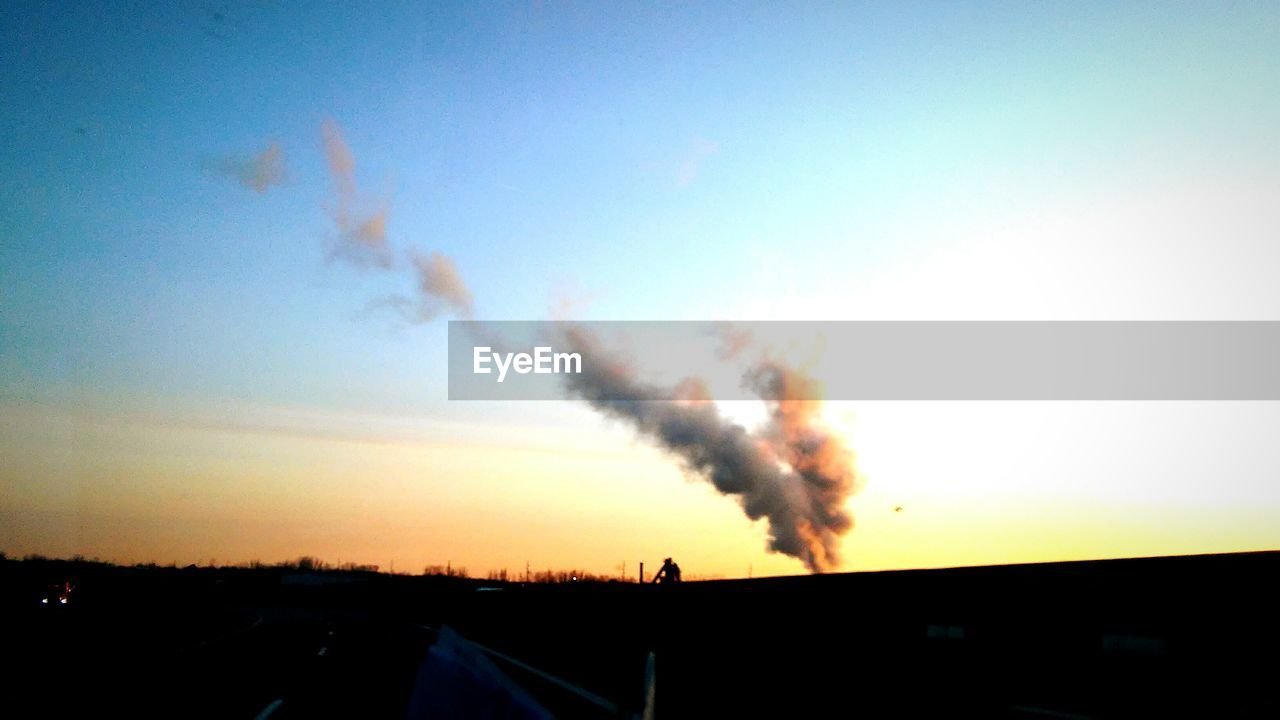 smoke - physical structure, sky, sunset, no people, built structure, smoke stack, architecture, outdoors, silhouette, clear sky, chimney, factory, nature, building exterior, day, vapor trail