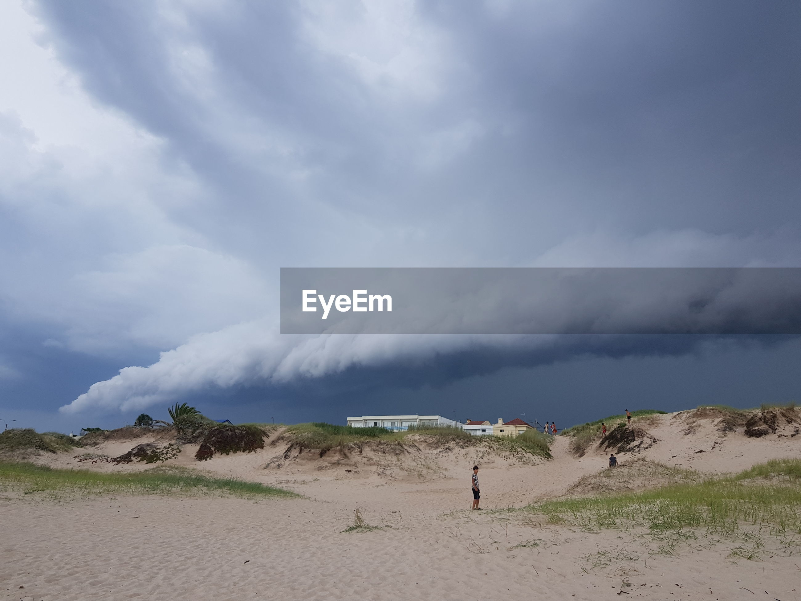SCENIC VIEW OF BEACH AGAINST STORM CLOUDS