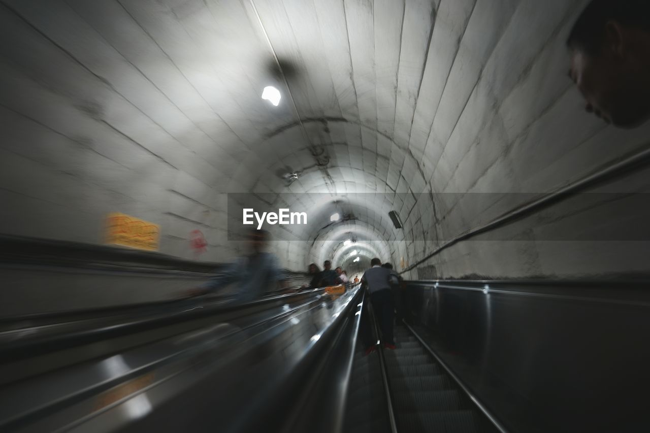 tunnel, indoors, illuminated, the way forward, real people, motion, light at the end of the tunnel, one person, rear view, underground, steps and staircases, transportation, blurred motion, subway station, built structure, lifestyles, architecture, technology, day, people