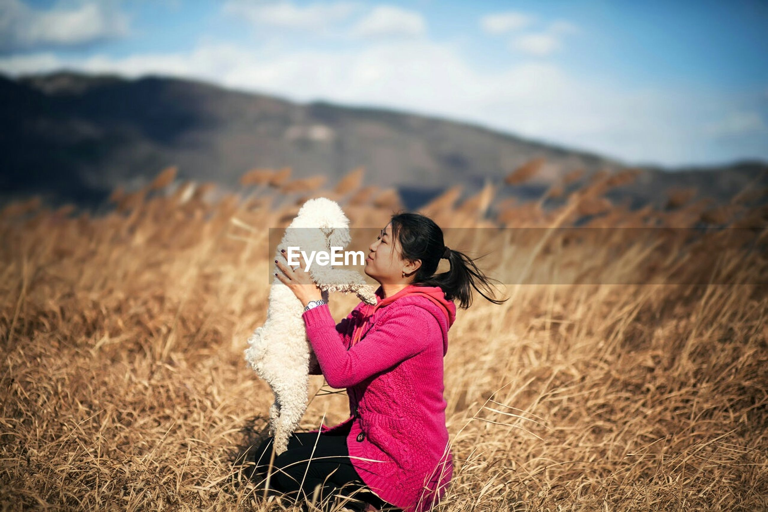 Woman holding white hairy dog on field during sunny day