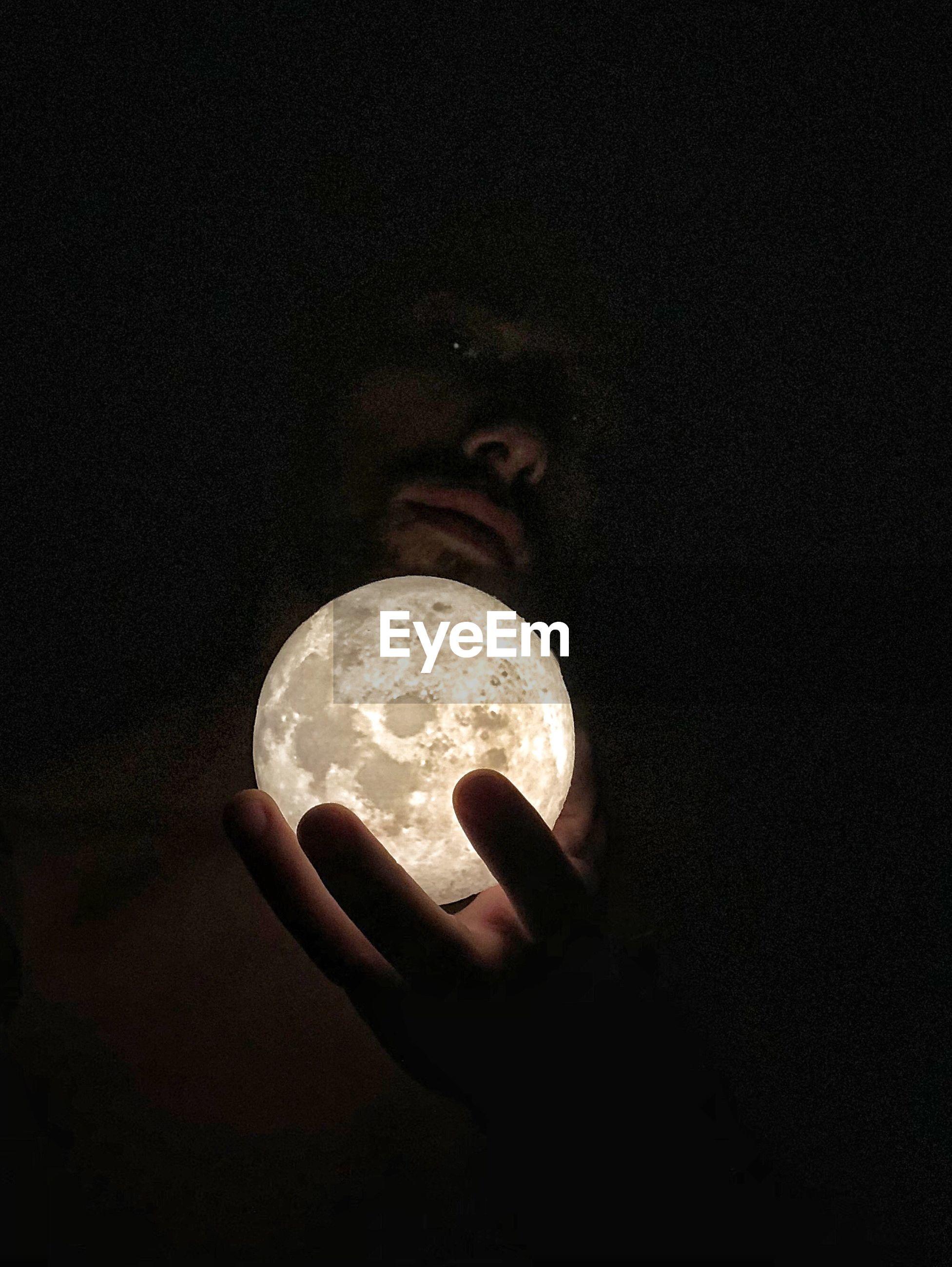 Digital composite image of man holding full moon against black background