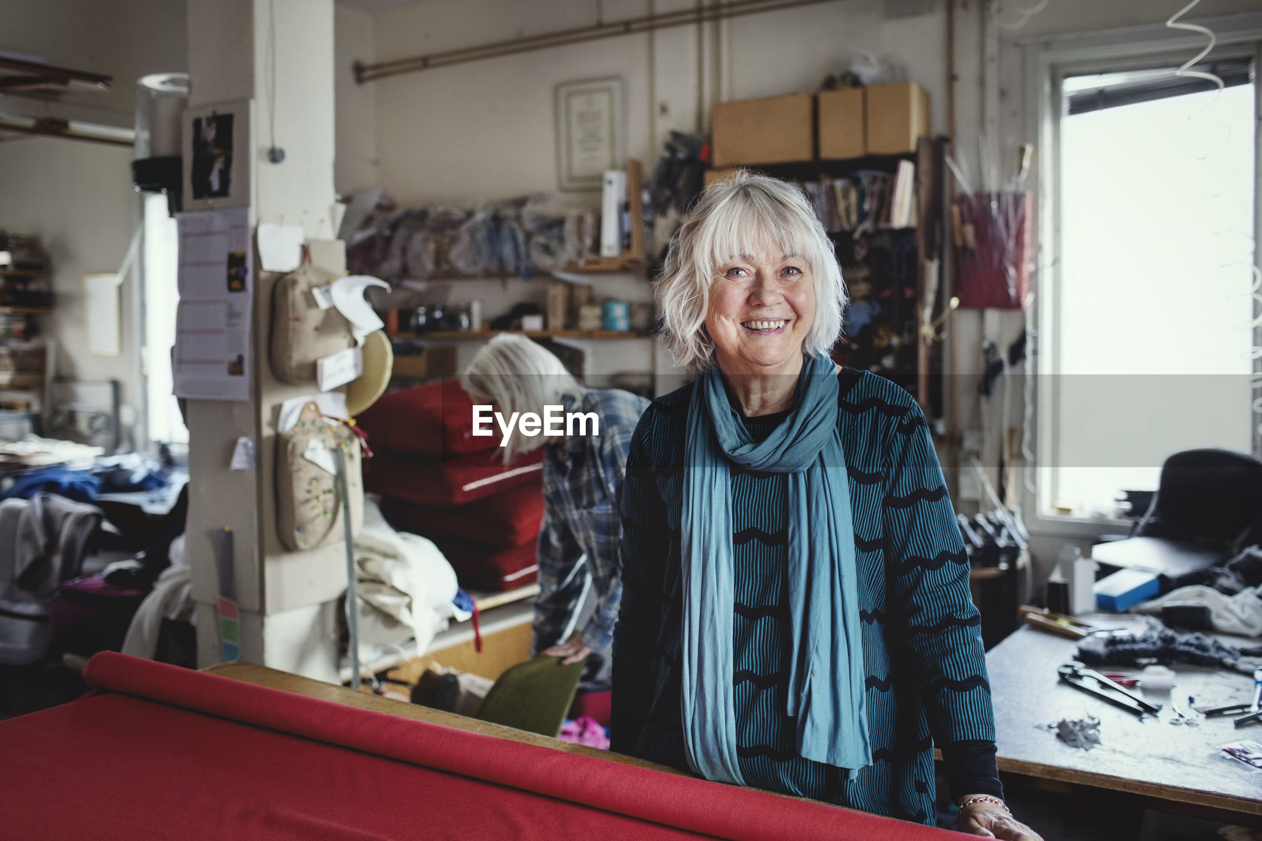 Portrait of smiling senior female standing at workbench in workshop