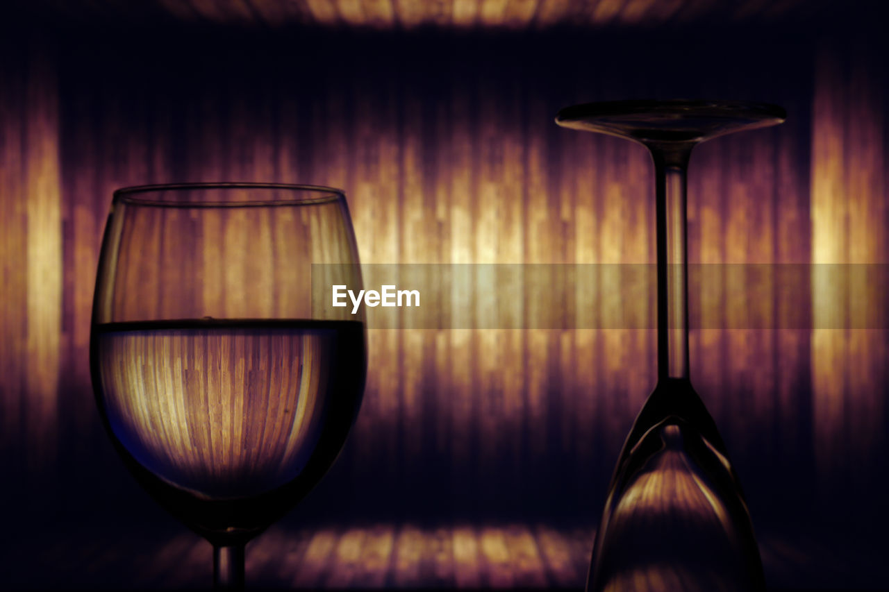 glass, drink, glass - material, refreshment, indoors, wineglass, food and drink, table, no people, wine, alcohol, still life, close-up, transparent, drinking glass, illuminated, wood - material, lighting equipment, focus on foreground, household equipment, electric lamp, nightlife