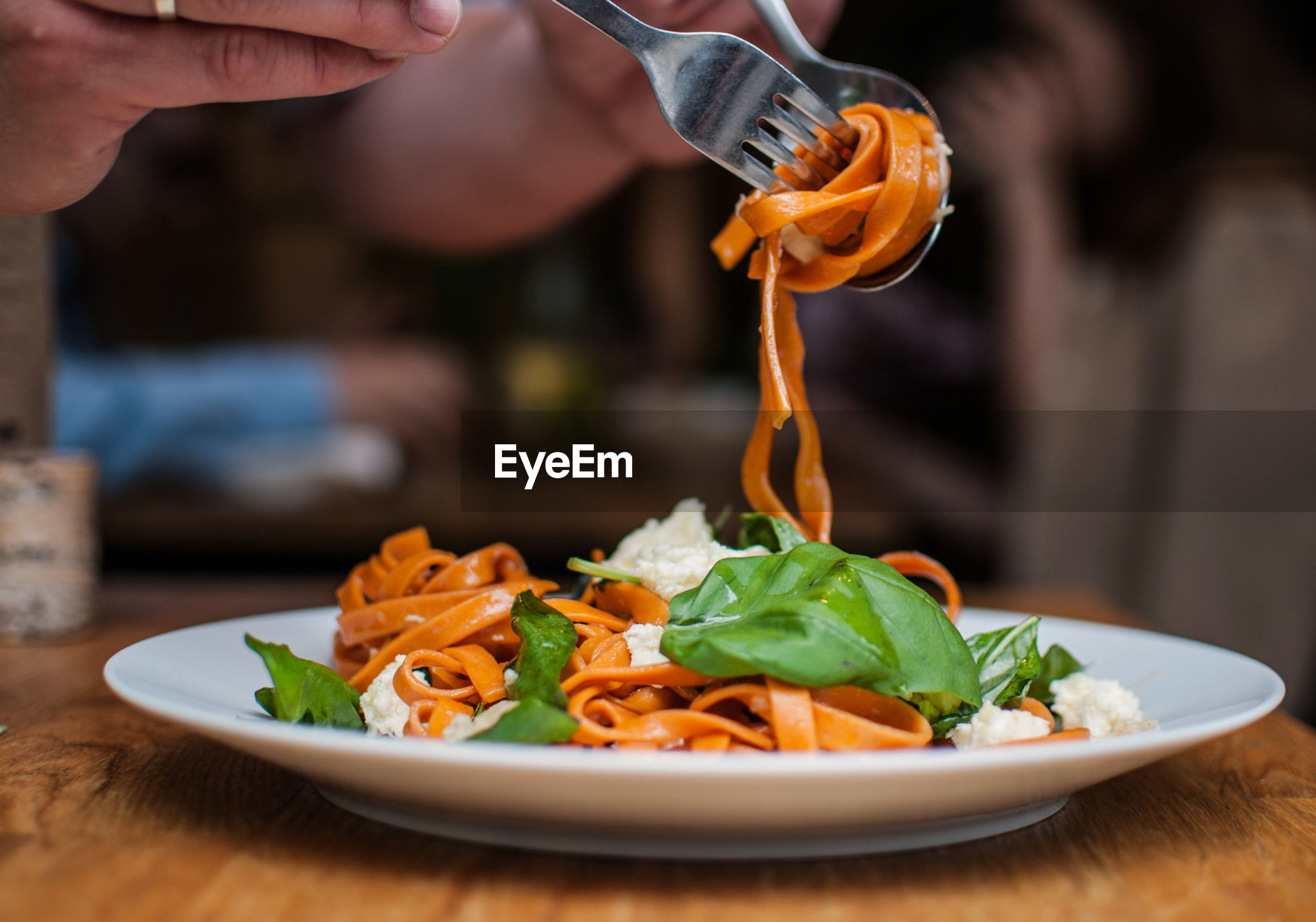 Cropped image of hands having pasta in restaurant