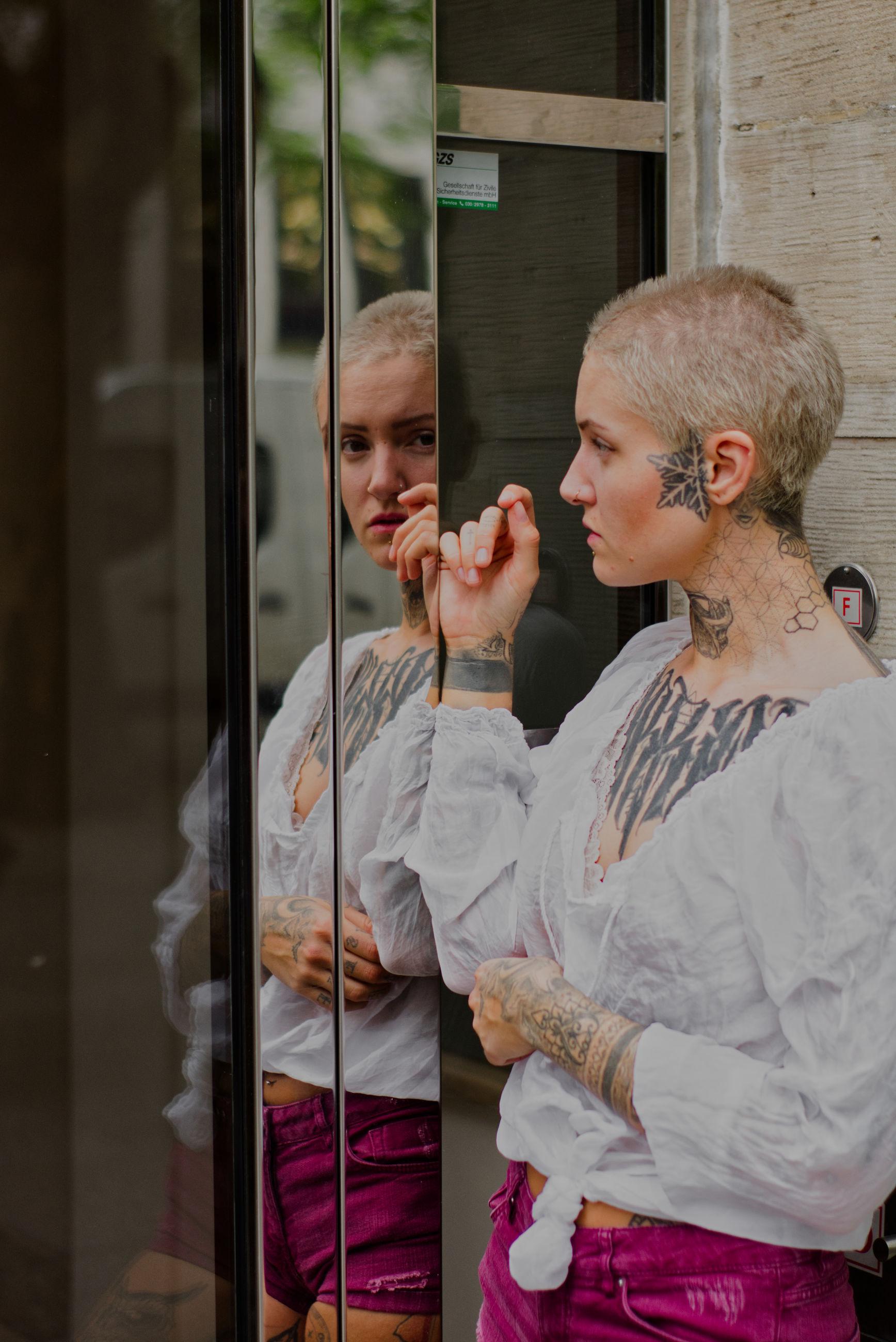 Portrait of tattooed woman reflecting on glass