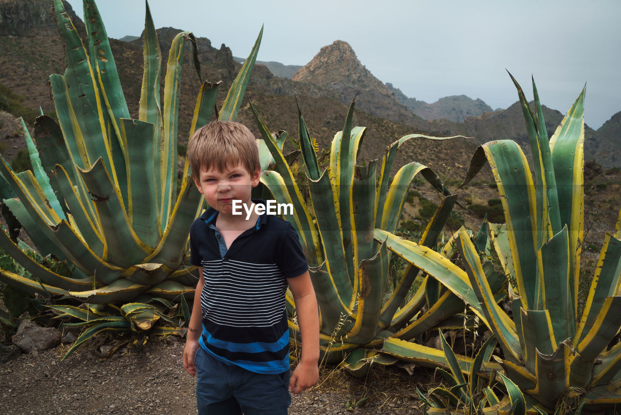 Angry funny boy blond is on the background of succulentswith large leaves.