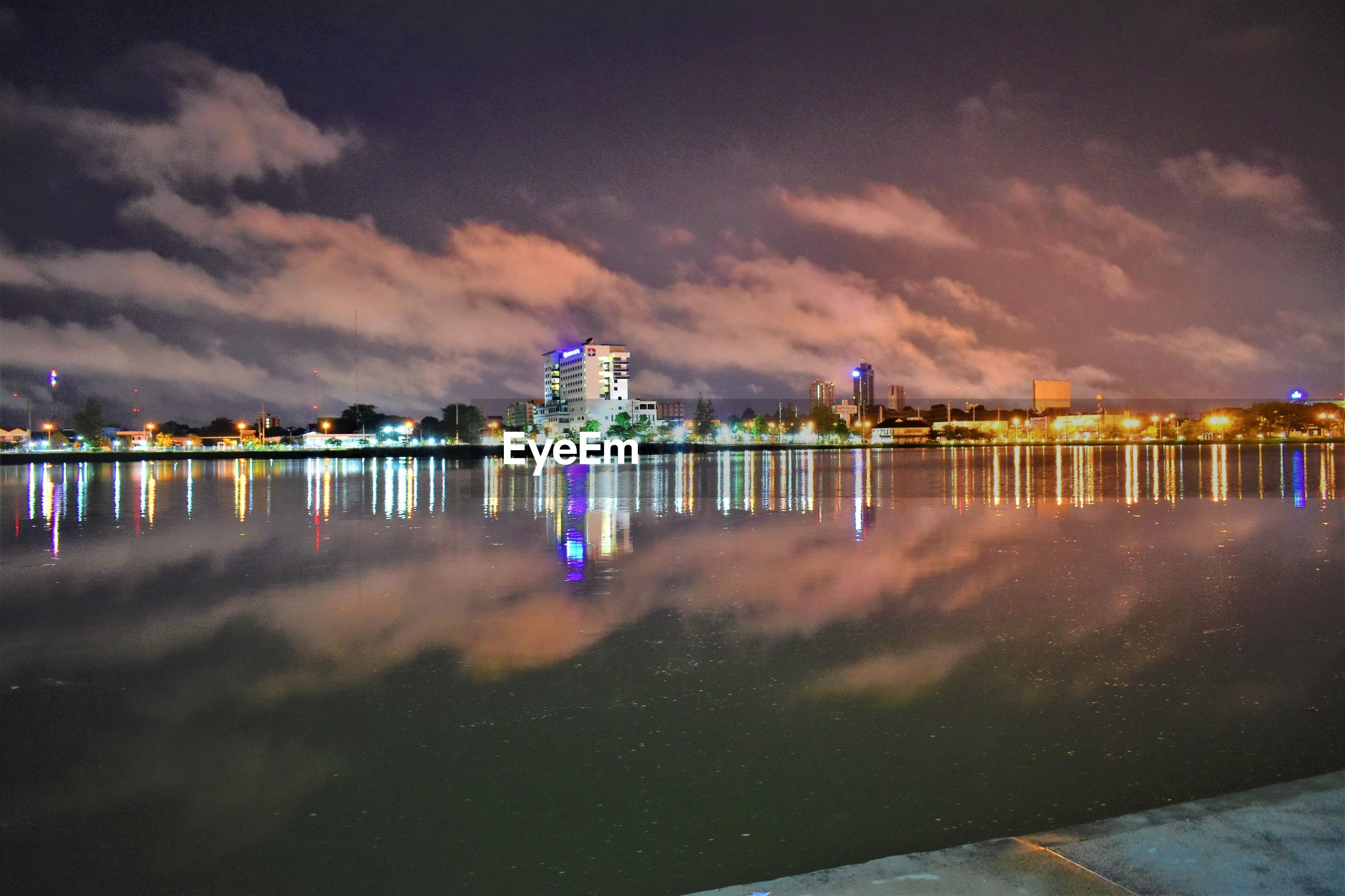 Illuminated buildings by lake against cloudy sky