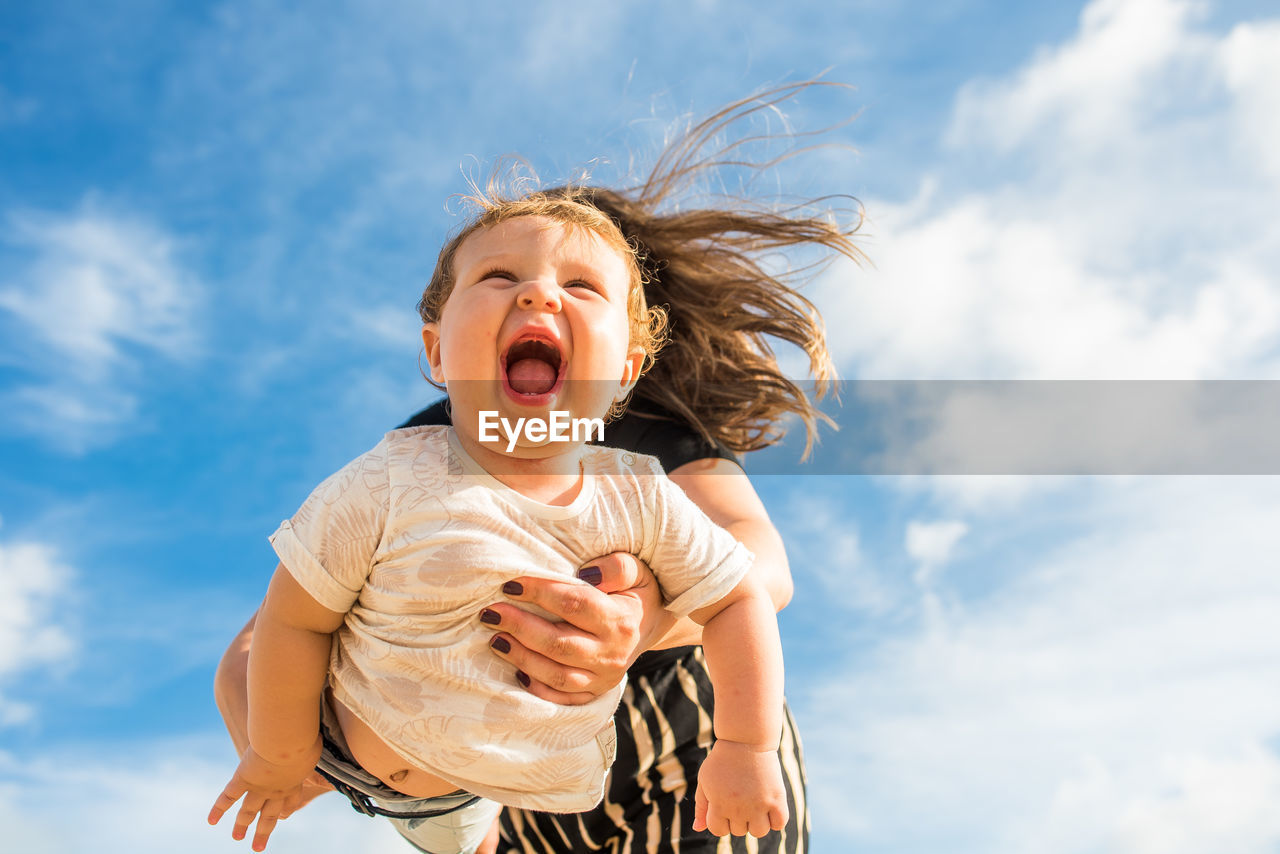 Low angle view of mother holding baby against sky