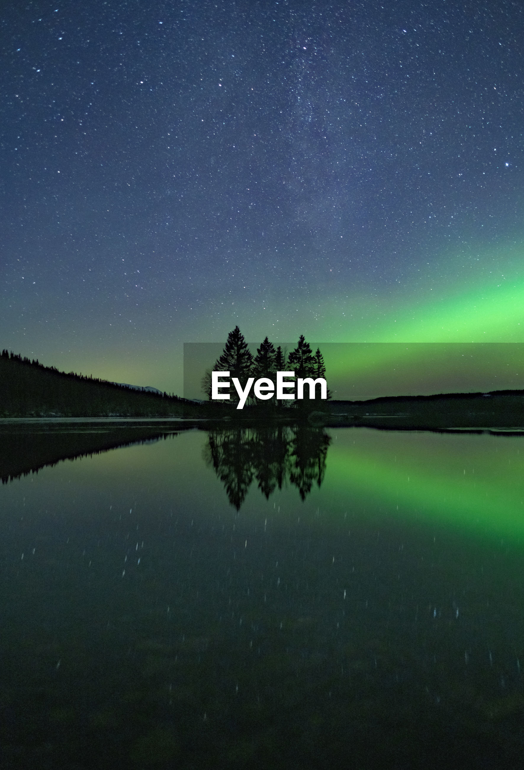 Starfield with aurora borealis reflections in a still lake with small island in the center
