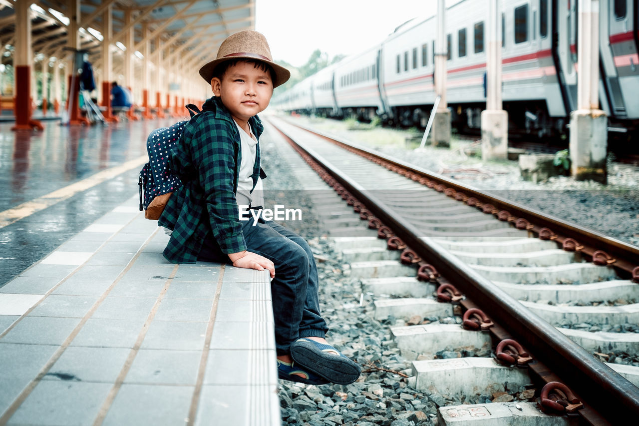 rail transportation, track, railroad track, one person, transportation, real people, looking at camera, mode of transportation, lifestyles, public transportation, clothing, portrait, railroad station, hat, young adult, casual clothing, leisure activity, railroad station platform, men, outdoors, waiting