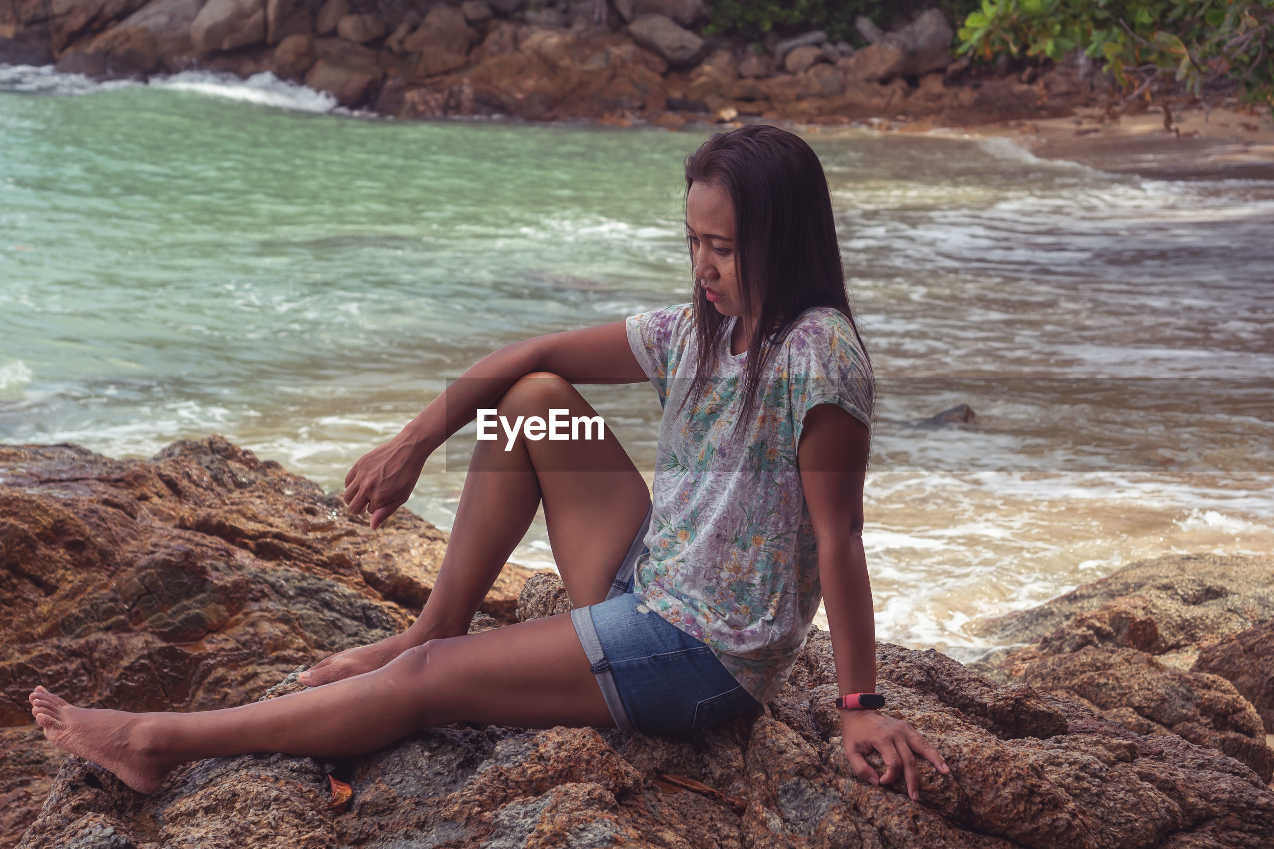 YOUNG WOMAN SITTING ON ROCK AT SHORE