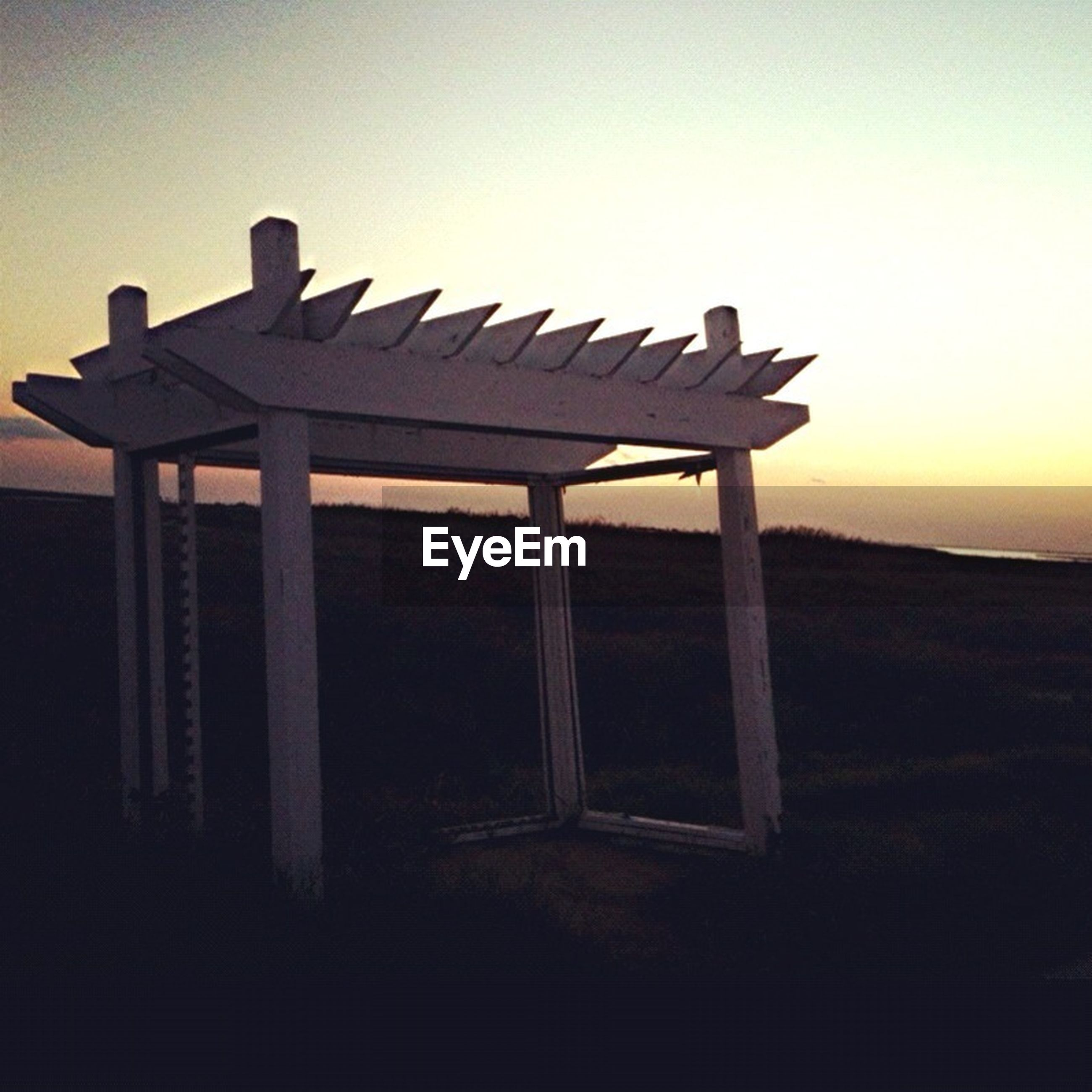 wood - material, wooden, wood, clear sky, tranquility, copy space, tranquil scene, sunset, bench, built structure, sky, no people, empty, nature, absence, field, old, silhouette, day, outdoors