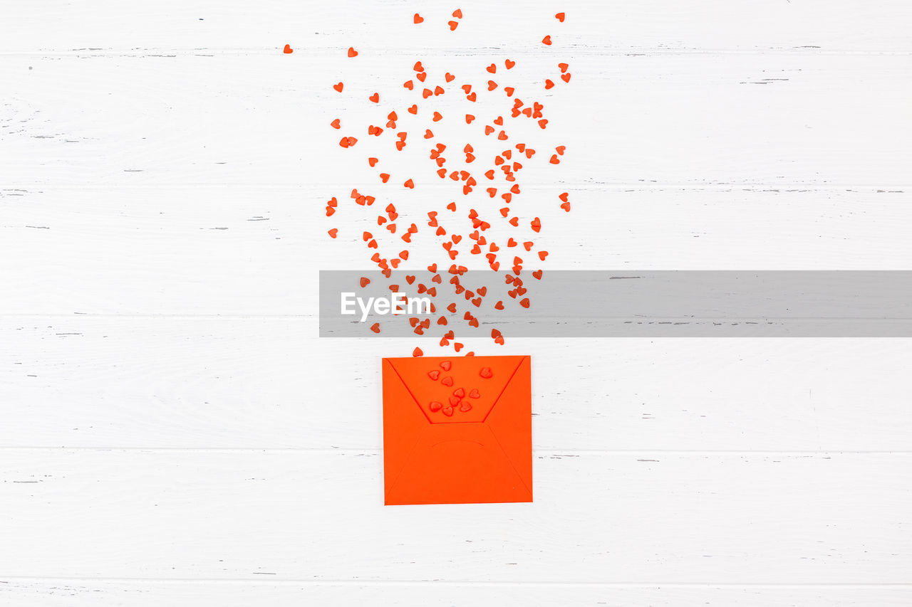 red, orange color, no people, wall - building feature, communication, indoors, paper, close-up, studio shot, still life, white color, text, reminder, table, shape, multi colored, creativity, number, day, vibrant color