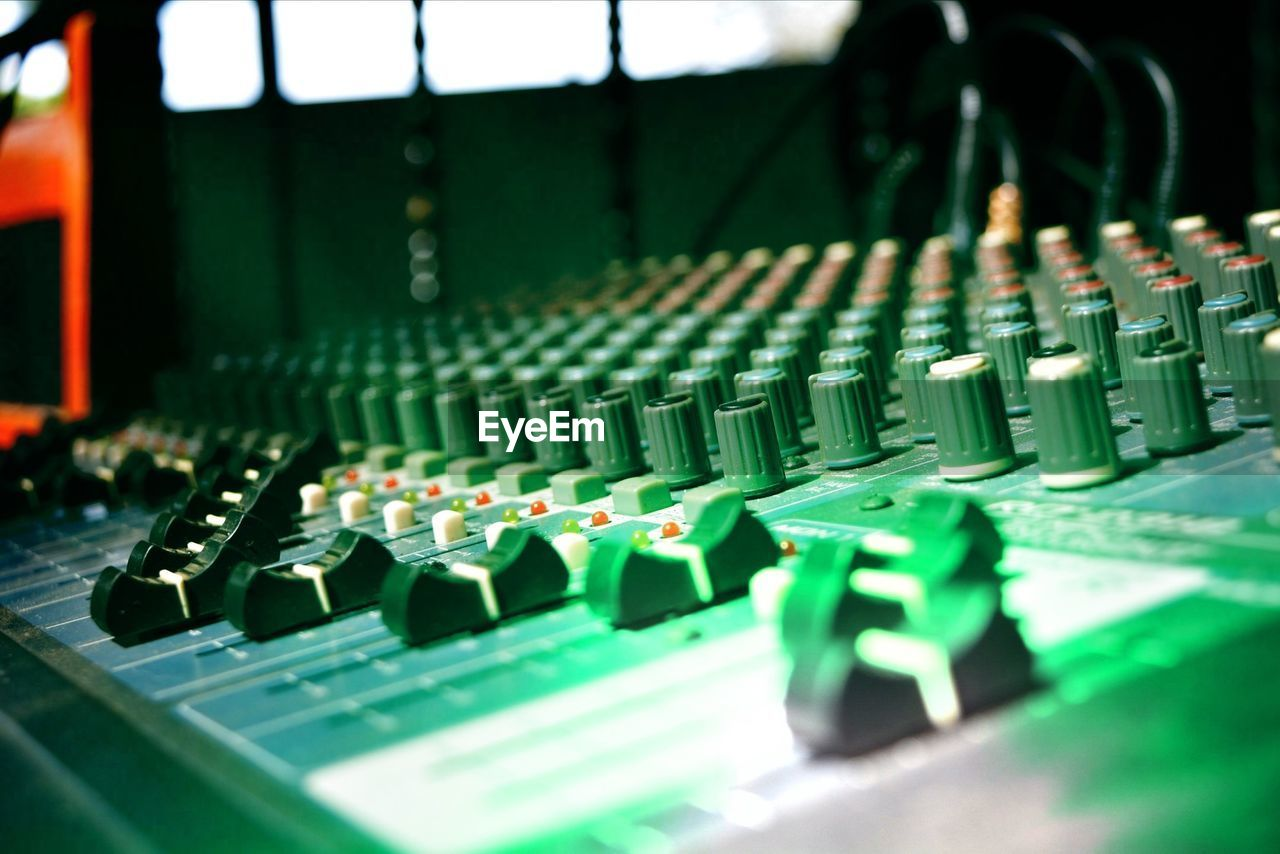 technology, sound recording equipment, music, audio equipment, sound mixer, studio, equipment, control, recording studio, indoors, arts culture and entertainment, close-up, selective focus, no people, green color, connection, control panel, communication, knob, industry, mixing, electrical equipment, complexity, audio electronics, electric mixer, nightlife
