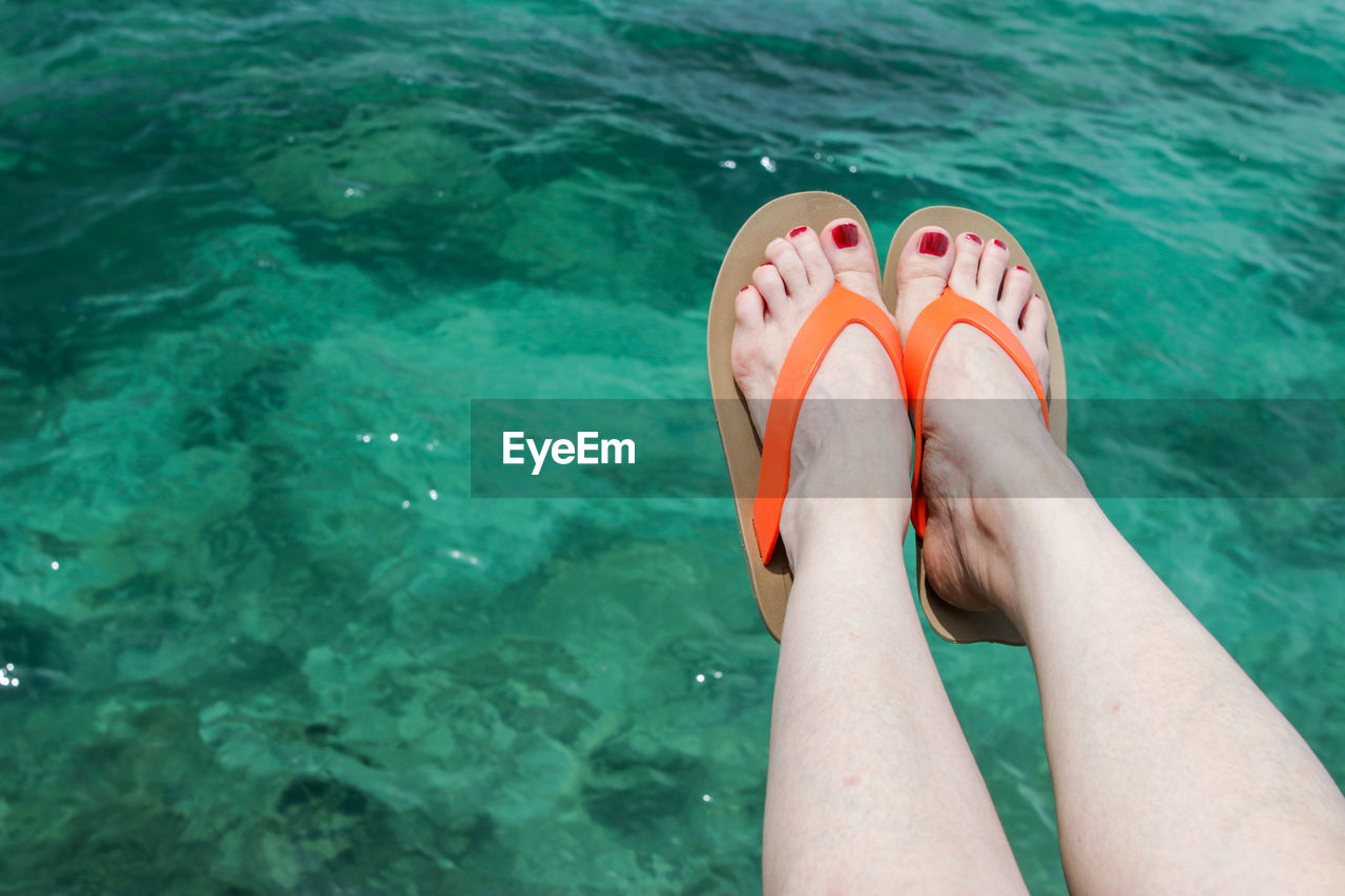 low section, human body part, body part, human leg, water, one person, personal perspective, leisure activity, nail polish, human foot, nail, real people, women, lifestyles, sea, day, adult, high angle view, nature, swimming pool, outdoors, toenail, slipper, turquoise colored