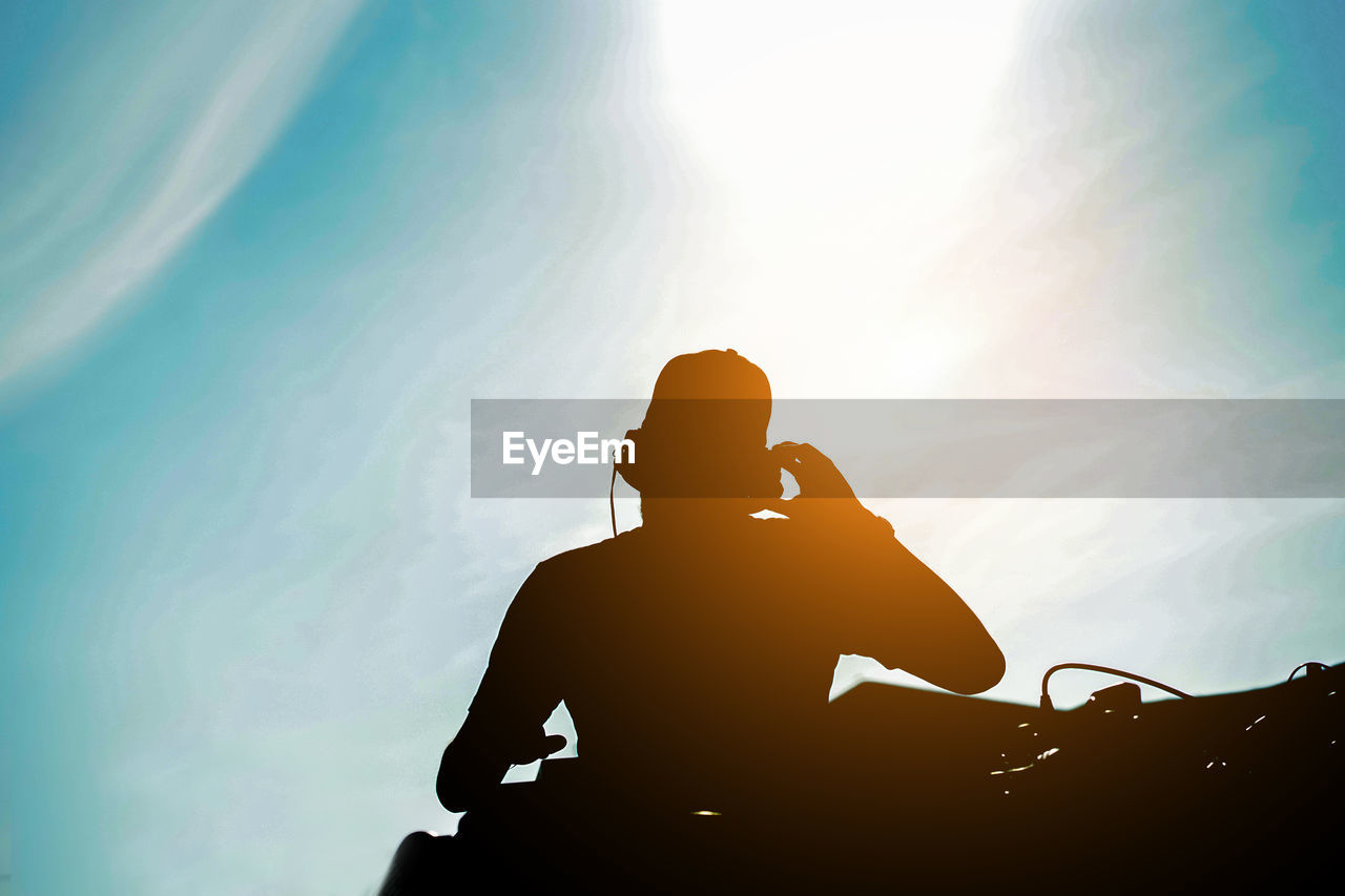 Low Angle View Of Silhouette Man Listening Music Against Sky
