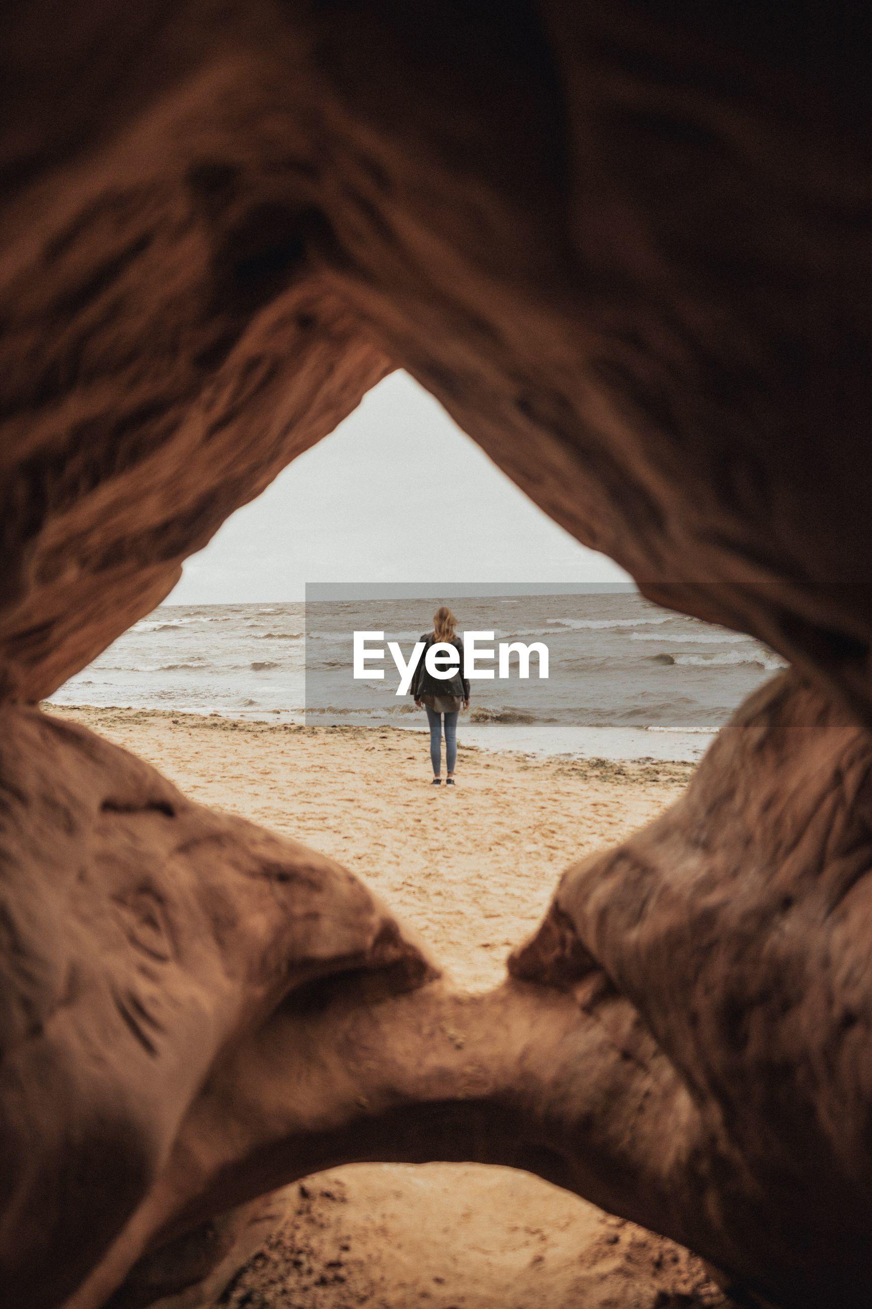 Rear view of woman standing at beach seen through rocks