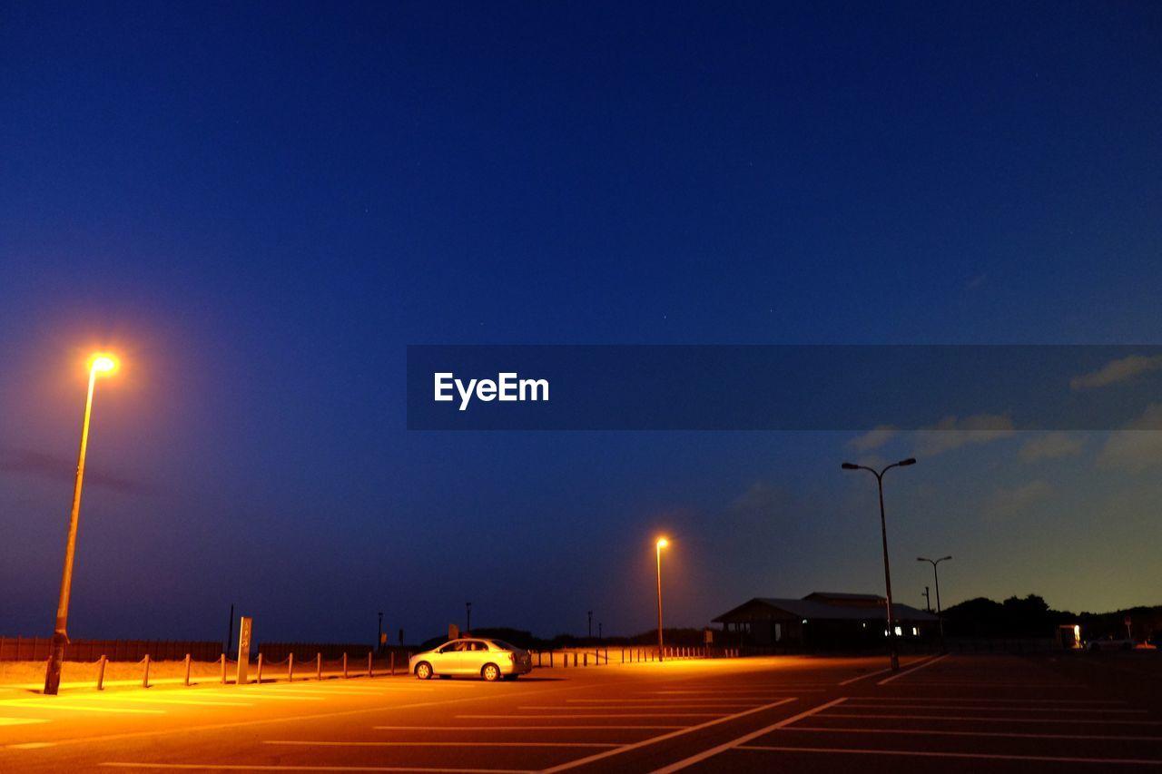 street light, illuminated, transportation, road, night, blue, lighting equipment, speed, car, land vehicle, sky, outdoors, no people