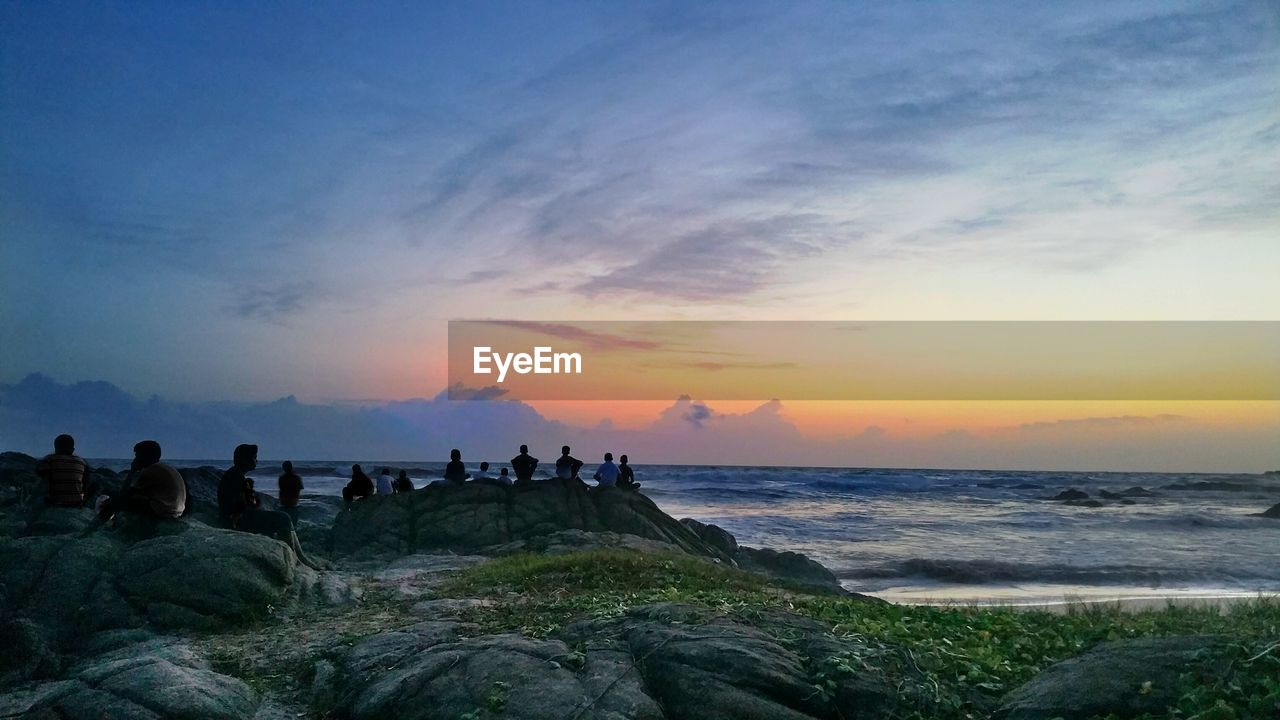 People Sitting At Beach Against Cloudy Sky During Sunset
