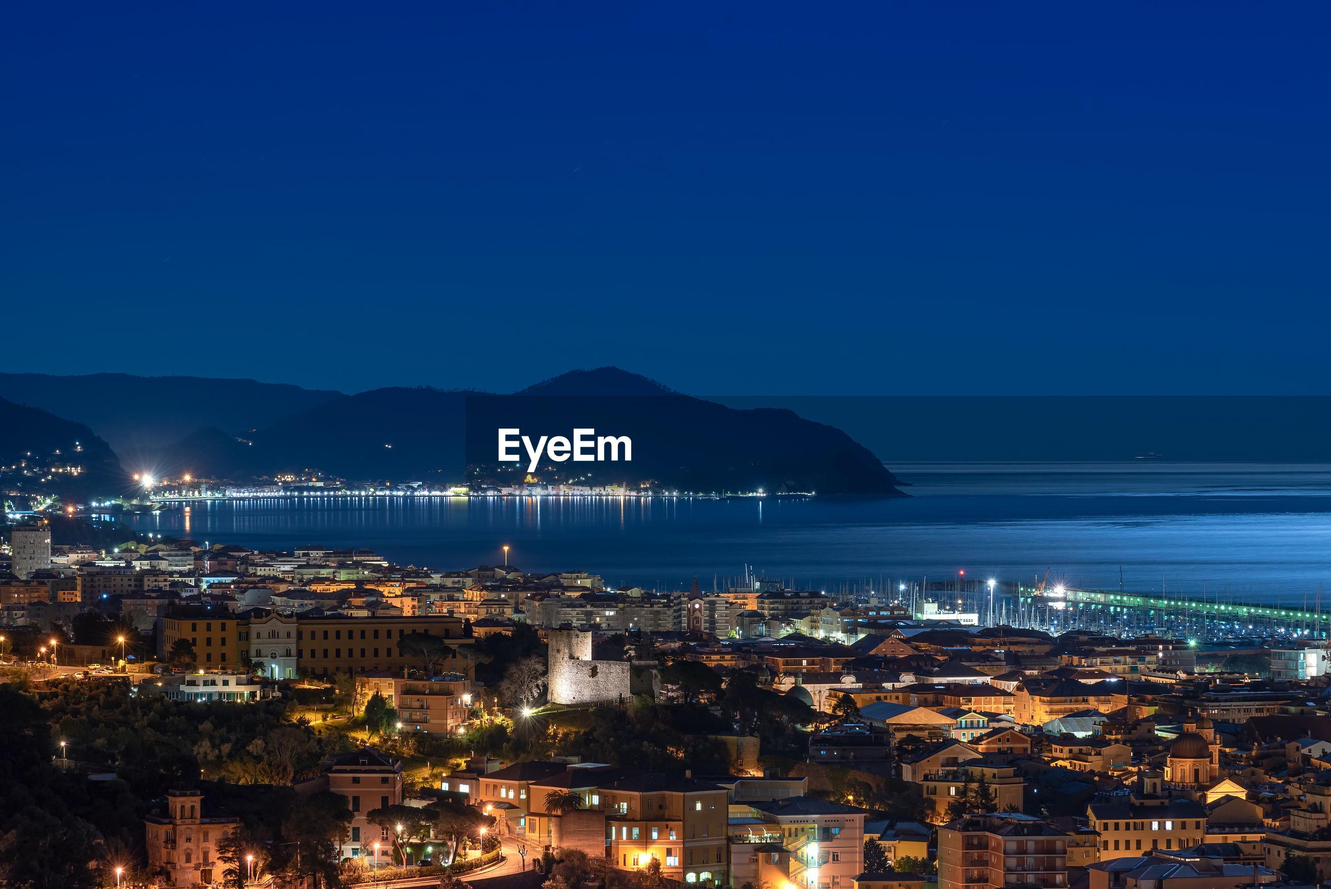 Illuminated city by sea against clear blue sky