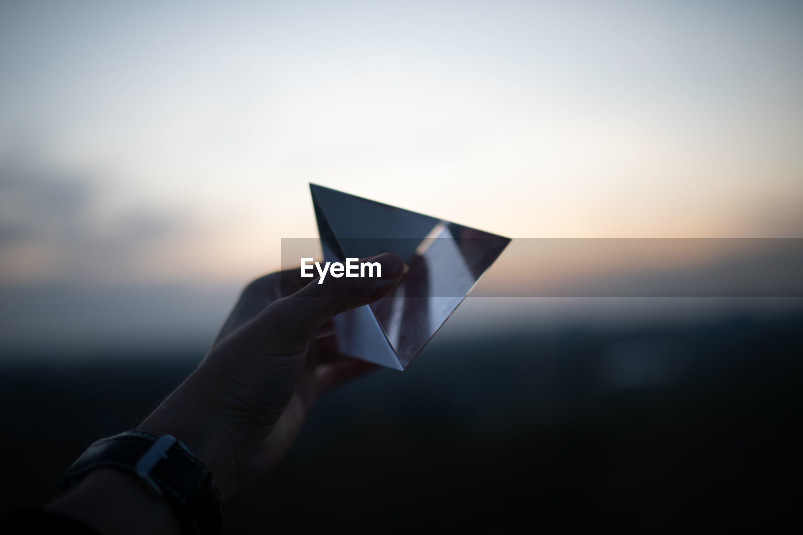 Cropped hand holding prism against sky during sunset