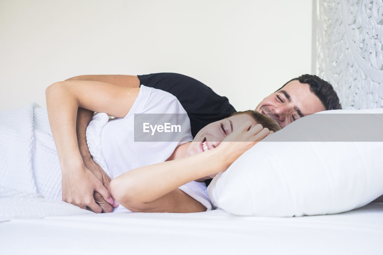 Smiling Couple Lying On Bed At Home