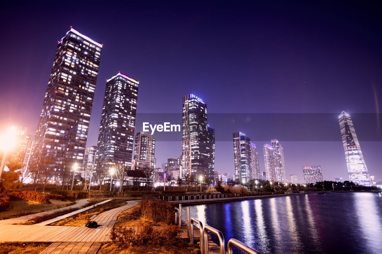 building exterior, architecture, built structure, night, illuminated, sky, office building exterior, city, skyscraper, building, tall - high, water, modern, nature, tower, landscape, urban skyline, travel destinations, office, no people, cityscape, financial district, outdoors, nightlife