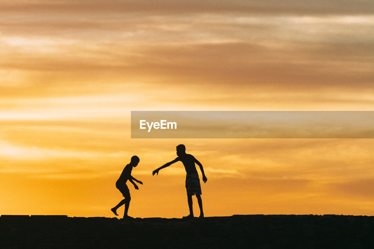 two people, silhouette, sunset, togetherness, real people, leisure activity, walking, men, sky, standing, playing, full length, nature, childhood, lifestyles, friendship, bonding, outdoors, beauty in nature, people